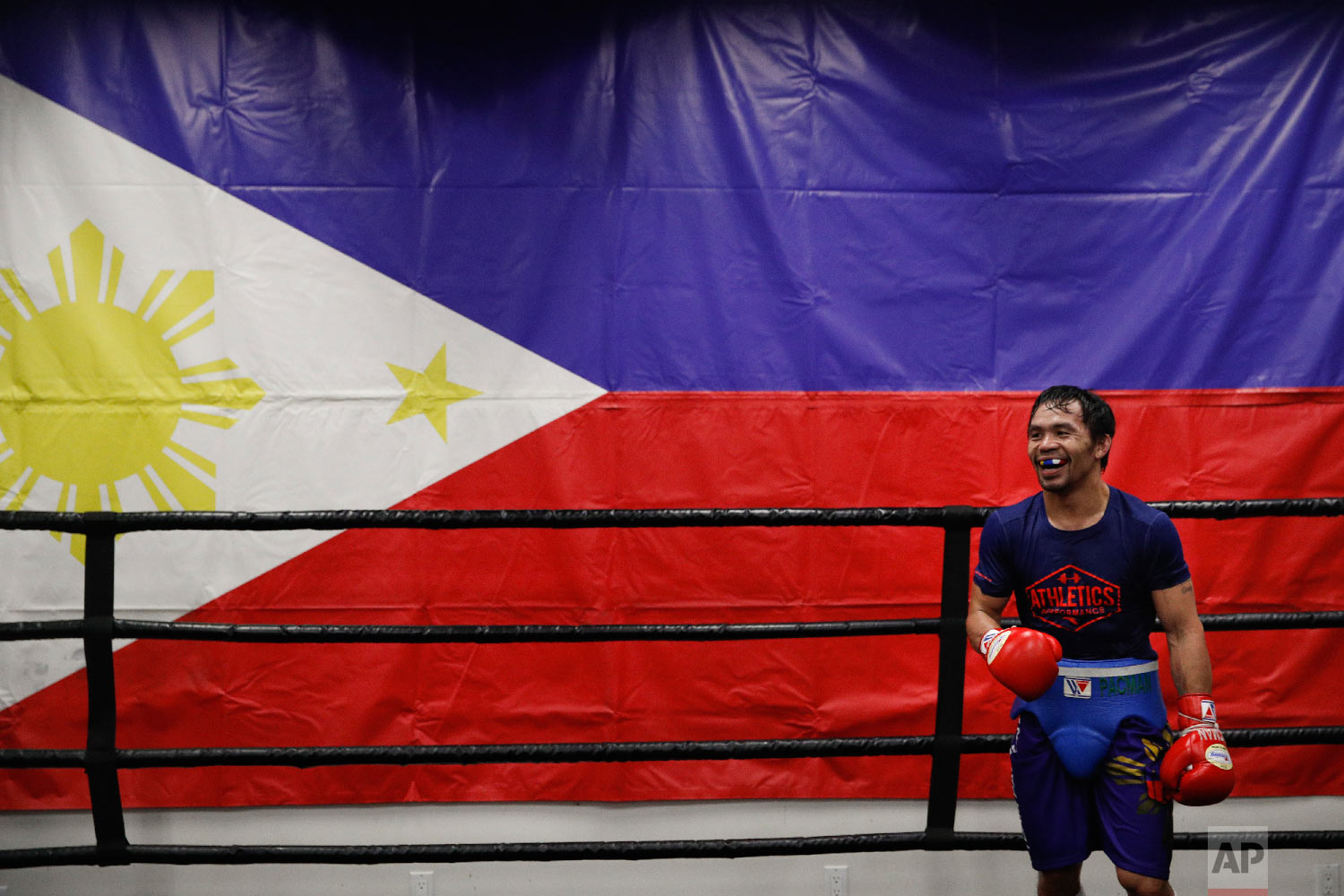 Standing in front of a large Filipino flag, boxer Manny Pacquiao smiles while training at the Wild Card Boxing Club on Jan. 14, 2019, in Los Angeles. (AP Photo/Jae C. Hong)