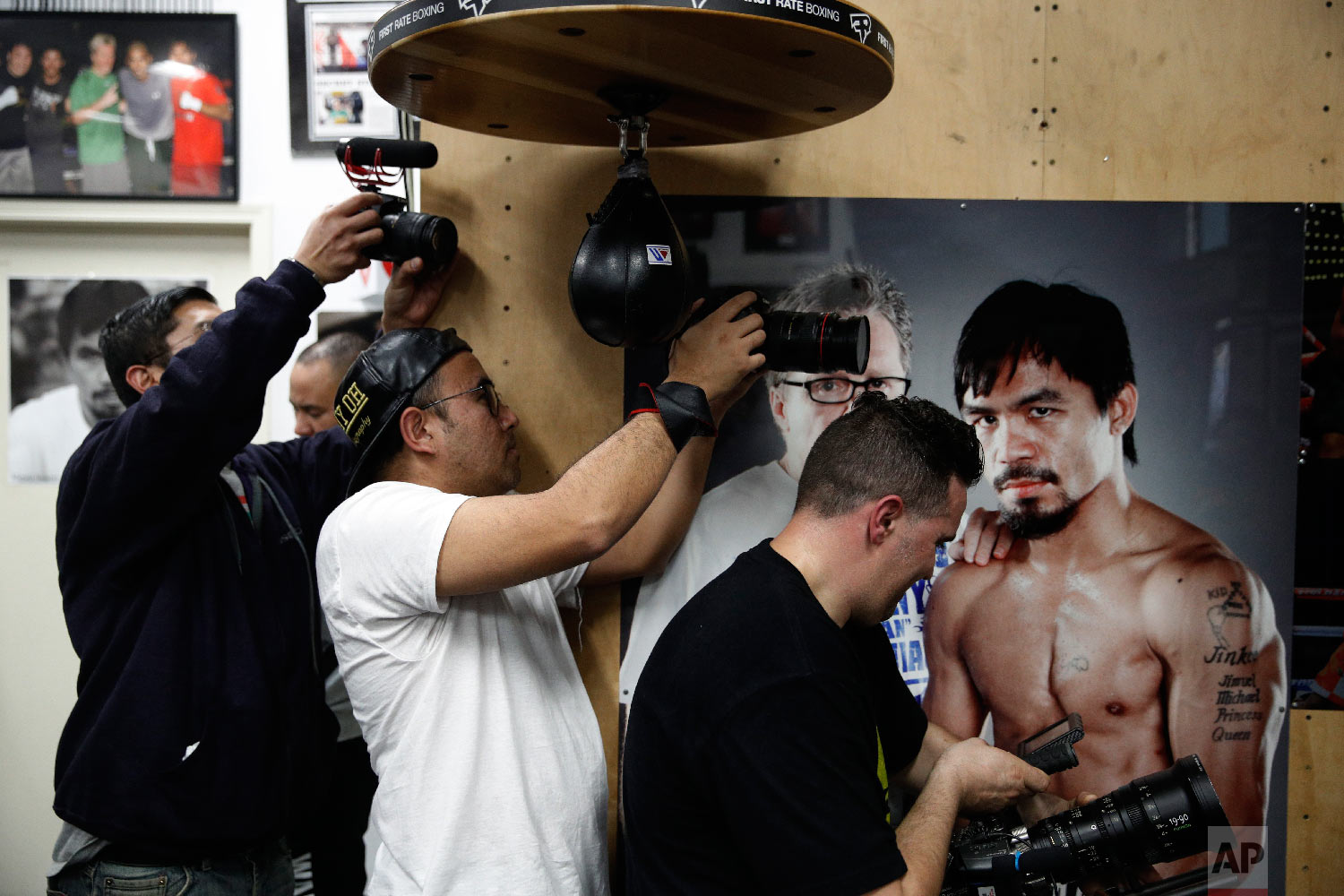 Film production crew members record as boxer Manny Pacquiao, not pictured, hits a speed bag at the Wild Card Boxing Club on Jan. 14, 2019, in Los Angeles. (AP Photo/Jae C. Hong)
