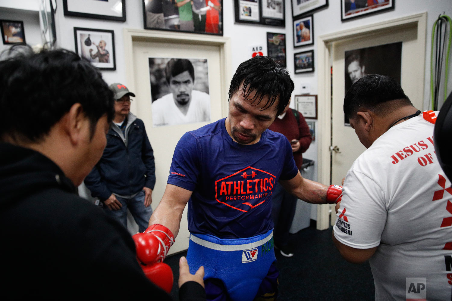 Soaked in sweat, boxer Manny Pacquiao gets his gloves removed after a workout at the Wild Card Boxing Club Monday, Jan. 14, 2019, in Los Angeles. (AP Photo/Jae C. Hong)