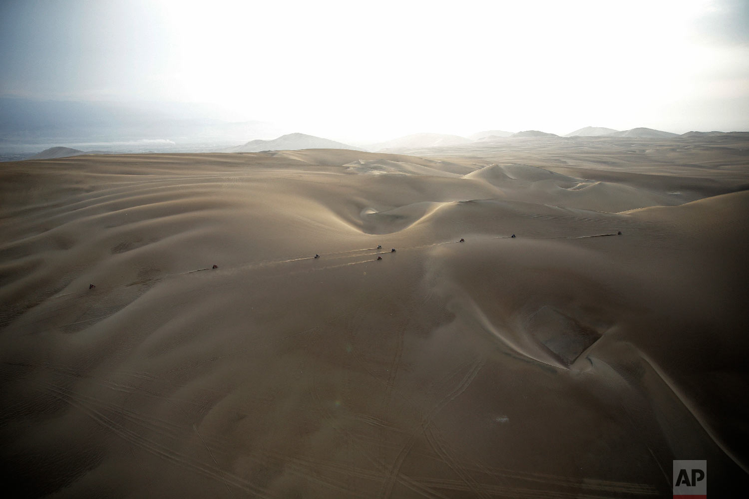 Competitors ride their motorbikes across the dunes during stage nine of the Dakar Rally in Pisco, Peru, Jan. 16, 2019. (AP Photo/Ricardo Mazalan)