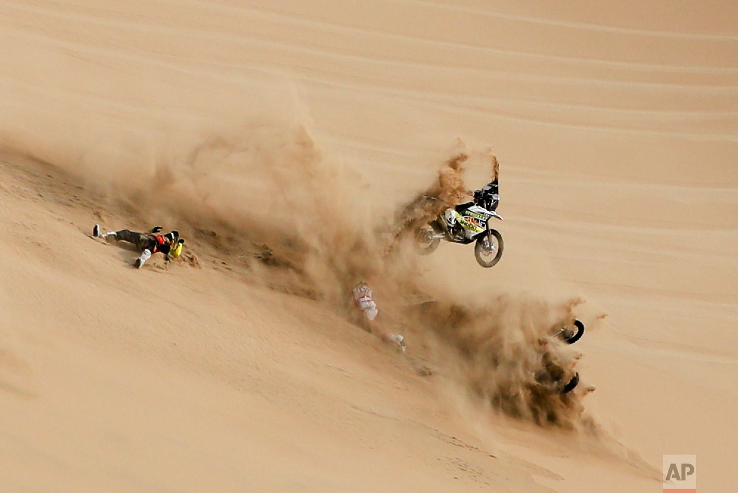 Husqvarna motorbike rider Jan Brabec of Czech Republic left, and KTM rider Cesar Pardo of Peru fall during the stage nine of the Dakar Rally in Pisco, Peru, Jan. 16, 2019. (AP Photo/Ricardo Mazalan)