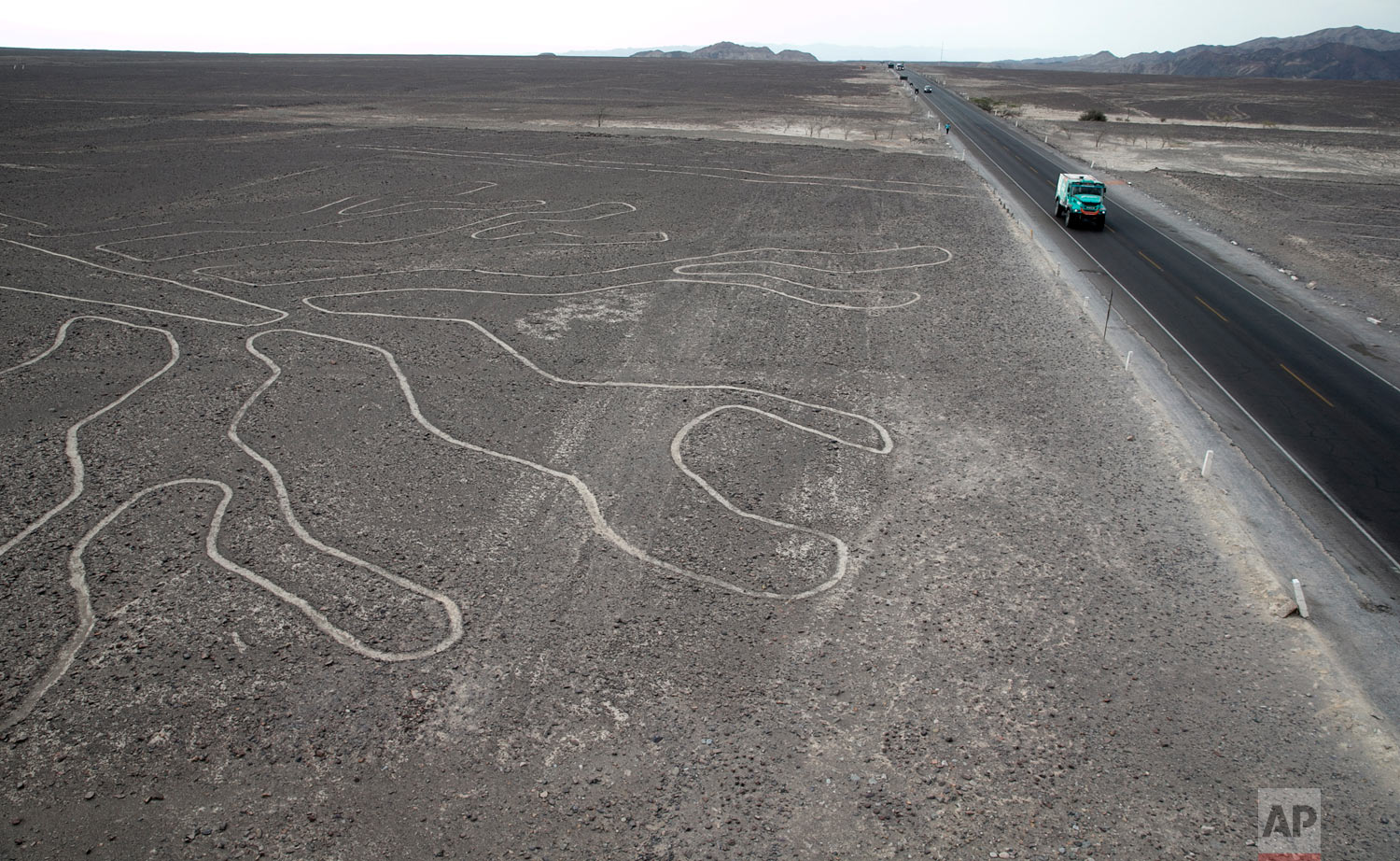 Driver Gerard De Rooy, of Netherlands, and co-drivers Darek Rodewald, of Poland, and Moises Torrallardona, of Spain, drive their Iveco truck on the Pan American highway along the Nazca Lines geoglyphs in Nazca, Peru, after finishing second in the second stage of the Dakar Rally between Pisco and San Juan de Marcona, Jan. 8, 2019. (AP Photo/Ricardo Mazalan)