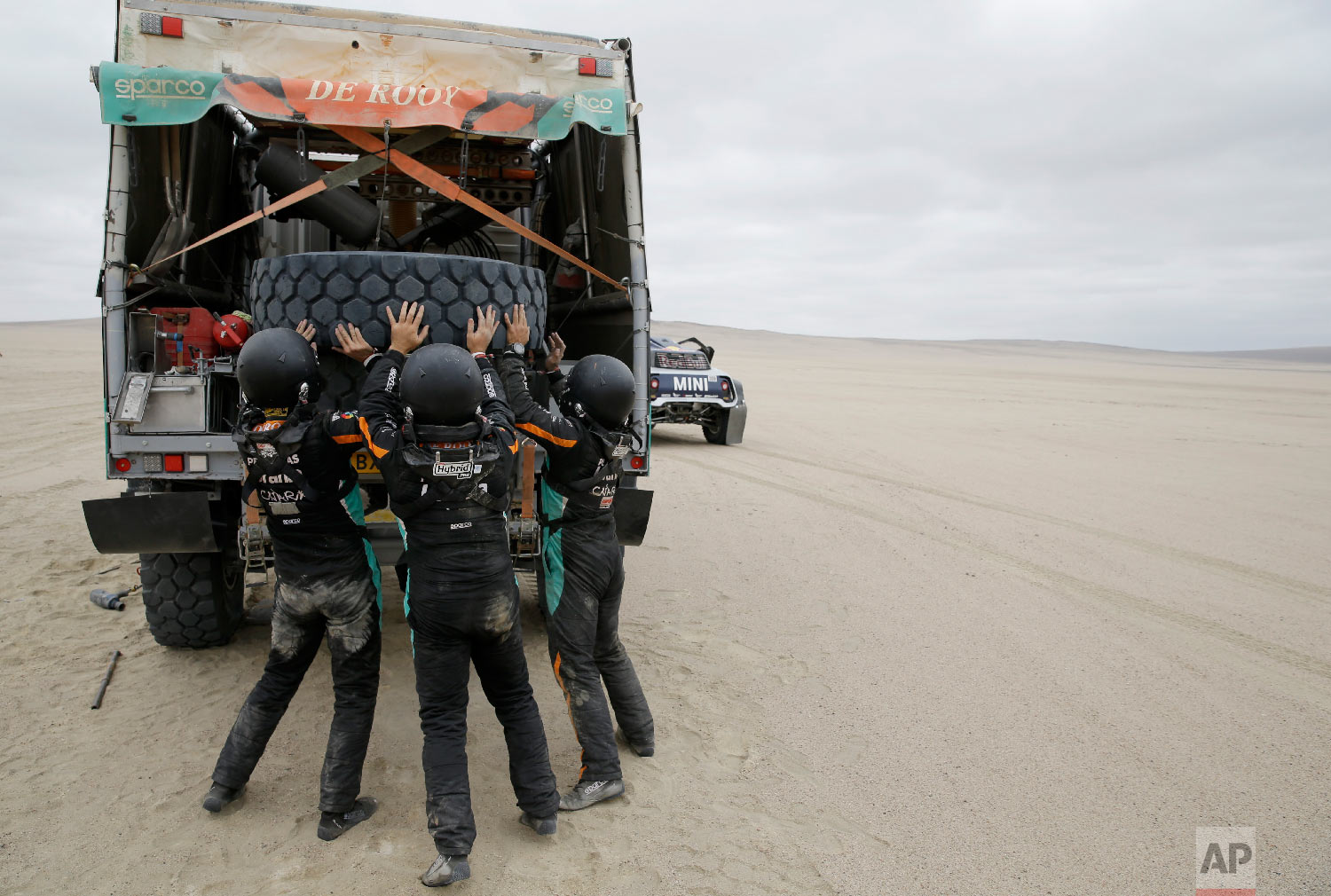 Driver Federico Villagra and co-drivers Arturo Yacopini and Ricardo Torlaschi, all of Argentina, lift a tyre onto their Iveco truck during the stage eight of the Dakar Rally between San Juan de Marcona and Pisco, Peru, Jan. 15, 2019. (AP Photo/Ricardo Mazalan)