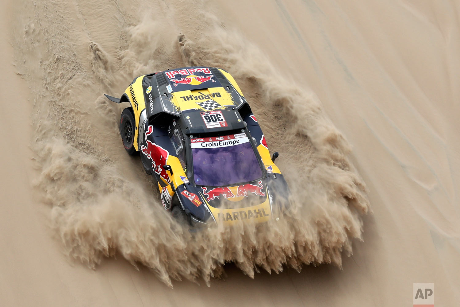 Driver Sebastien Loeb, of France, and co-driver Daniel Elena, of Monaco, race their Peugeot during the first stage of the Dakar Rally between Lima and Pisco, Peru, Jan. 7, 2019. (AP Photo/Ricardo Mazalan)