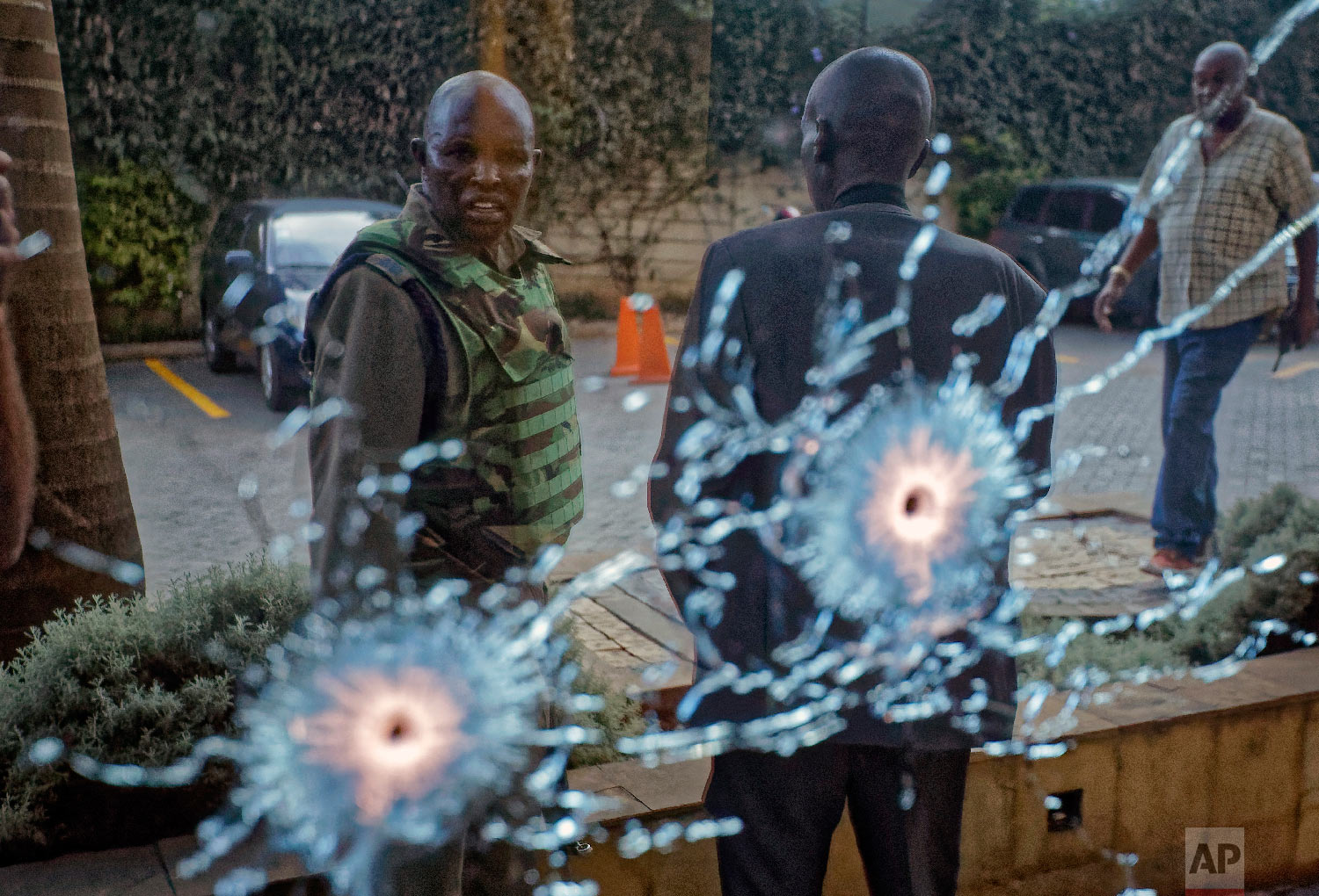 A member of the security forces is seen reflected in a window as he looks at bullet-holes, at a hotel complex in Nairobi, Kenya, Jan. 15, 2019. (AP Photo/Ben Curtis)
