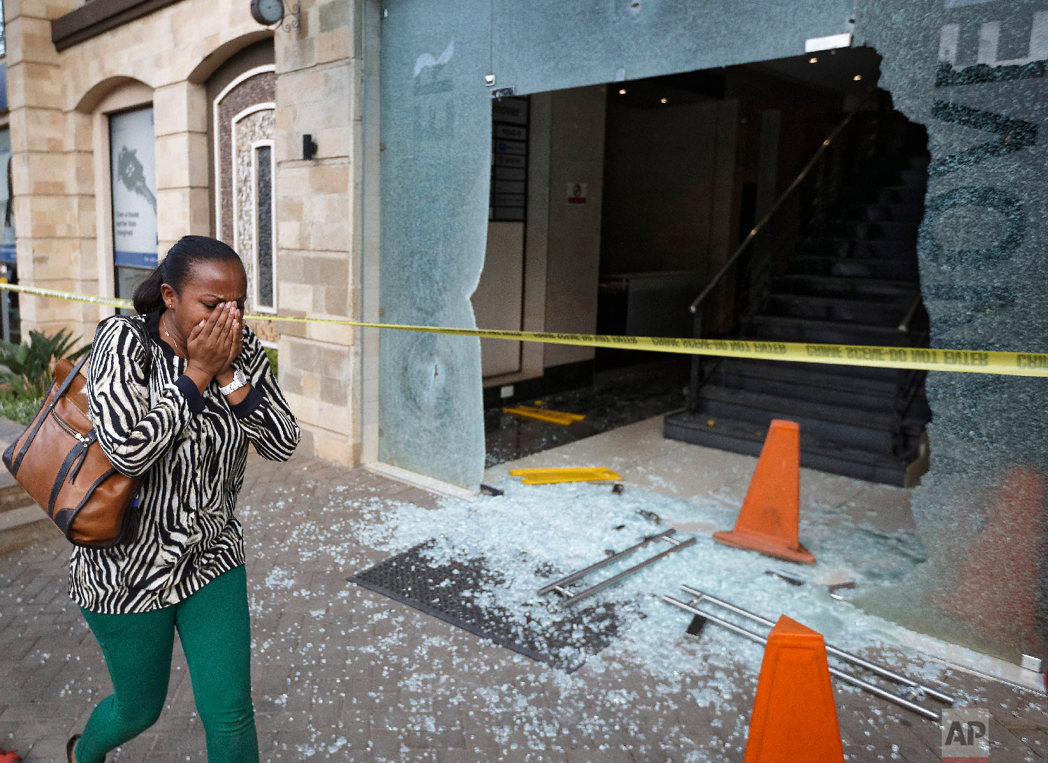 A woman reacts as she flees the scene at a hotel complex in Nairobi, Kenya, Jan. 15, 2019. (AP Photo/Ben Curtis)