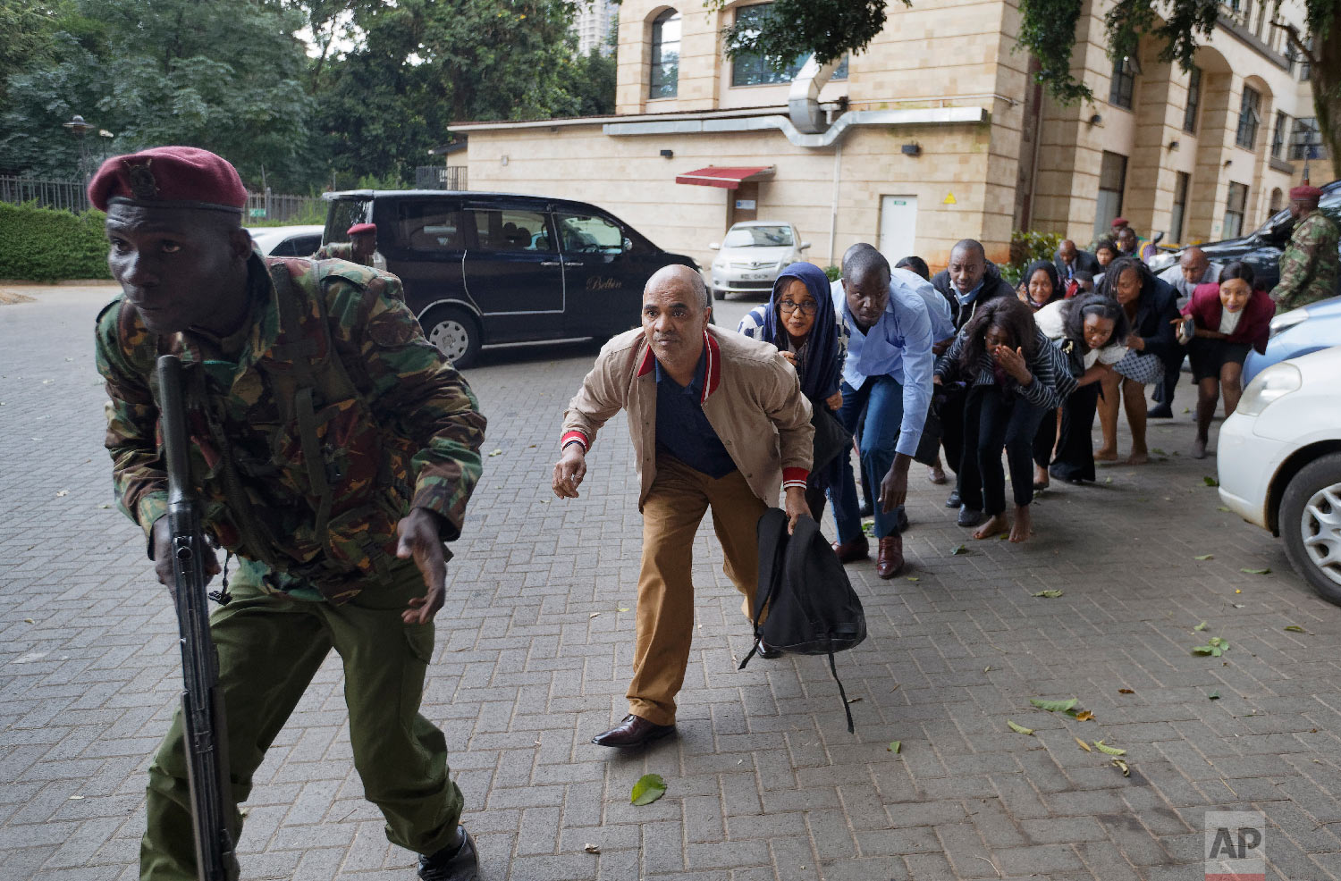 Civilians who had been hiding in buildings flee under the direction of a member of security forces at a hotel complex in Nairobi, Kenya, Jan. 15, 2019. (AP Photo/Ben Curtis)