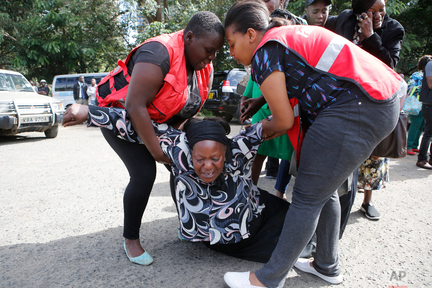 Kenya Red Cross personnel helps a woman reacting after learning of a family member killed during a recent terrorist attack, Jan. 16 2019, at the Chiromo Mortuary, Nairobi, Kenya. (AP Photo/Brian Inganga)