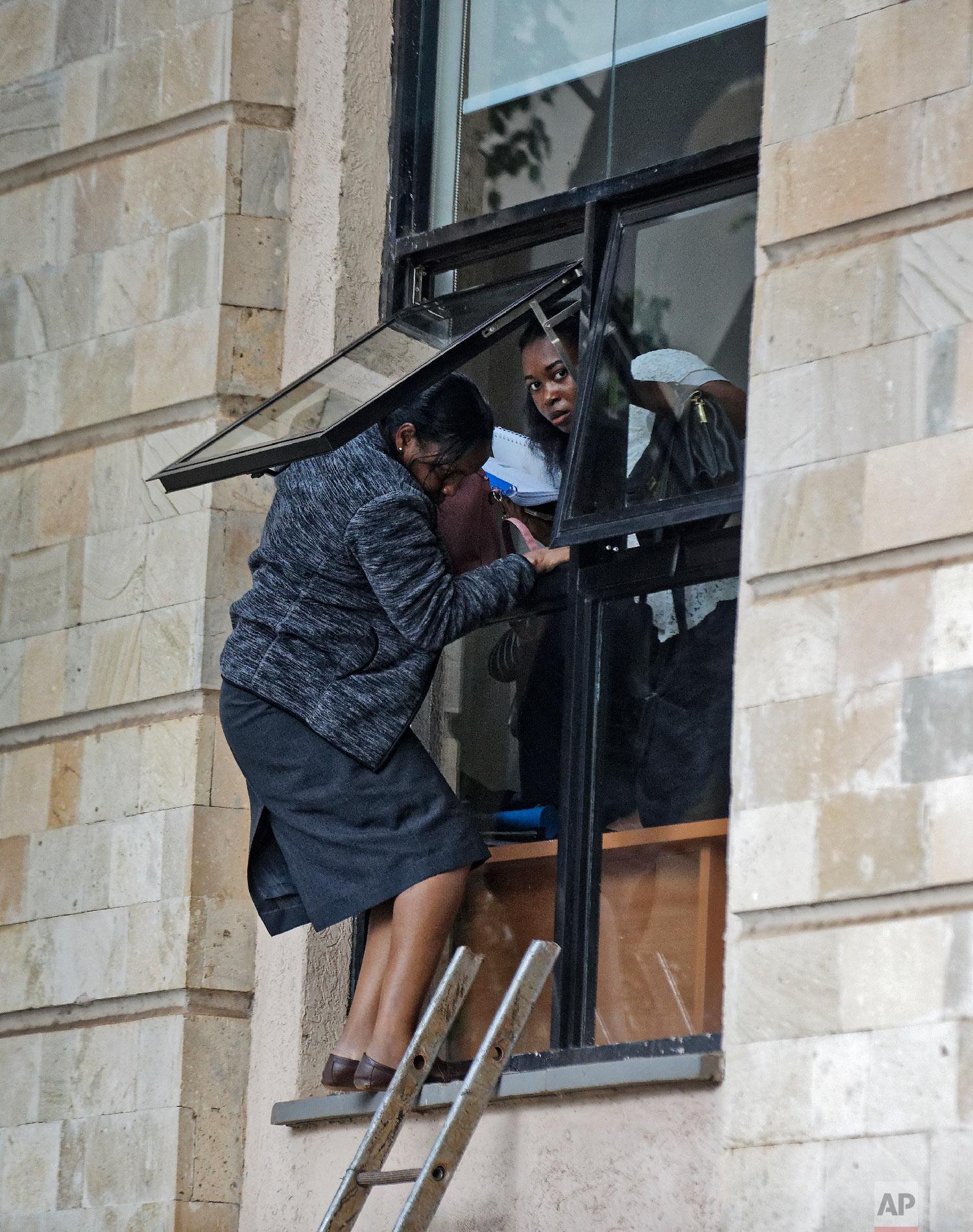 Civilians flee through a window at a hotel complex in Nairobi, Kenya, Jan. 15, 2019. (AP Photo/Ben Curtis)