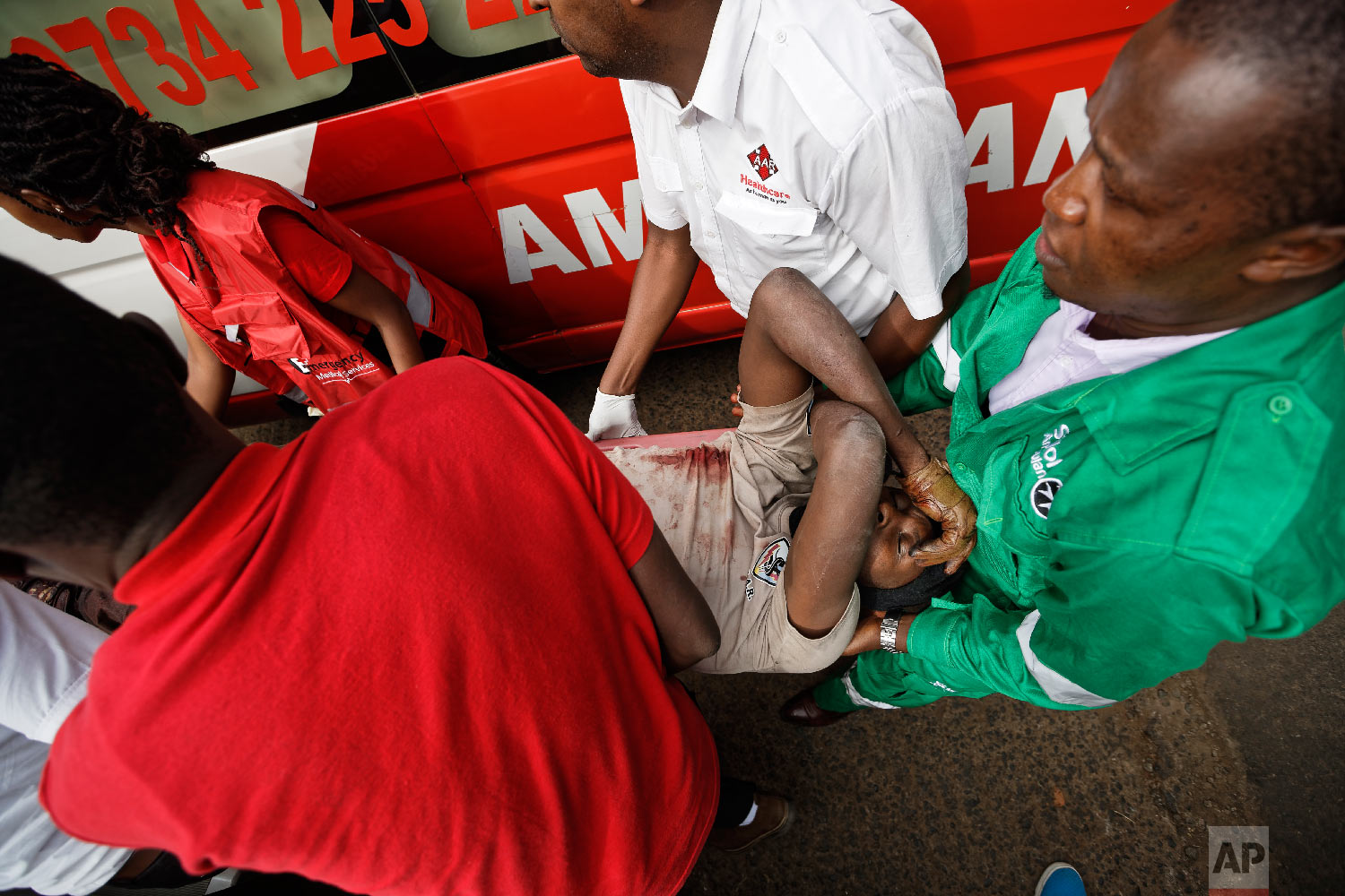 A wounded member of Kenyan special forces is carried from a US embassy diplomatic vehicle into an ambulance by paramedics at the scene Jan. 16, 2019 in Nairobi, Kenya. (AP Photo/Ben Curtis)
