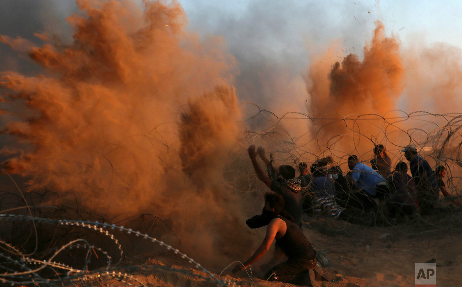 Protesters spread sand in the air while others burn tires near the fence of the Gaza Strip border with Israel during a protest east of Khan Younis, southern Gaza Strip, Oct. 12, 2018. (AP Photo/Adel Hana)