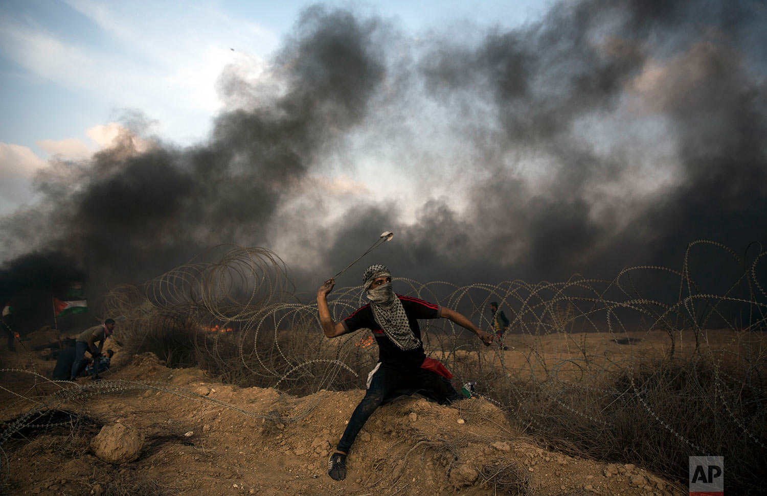 A Palestinian protester hurls stones towards Israeli troops at the Gaza Strip's border with Israel, Oct. 19, 2018. (AP Photo/Khalil Hamra)