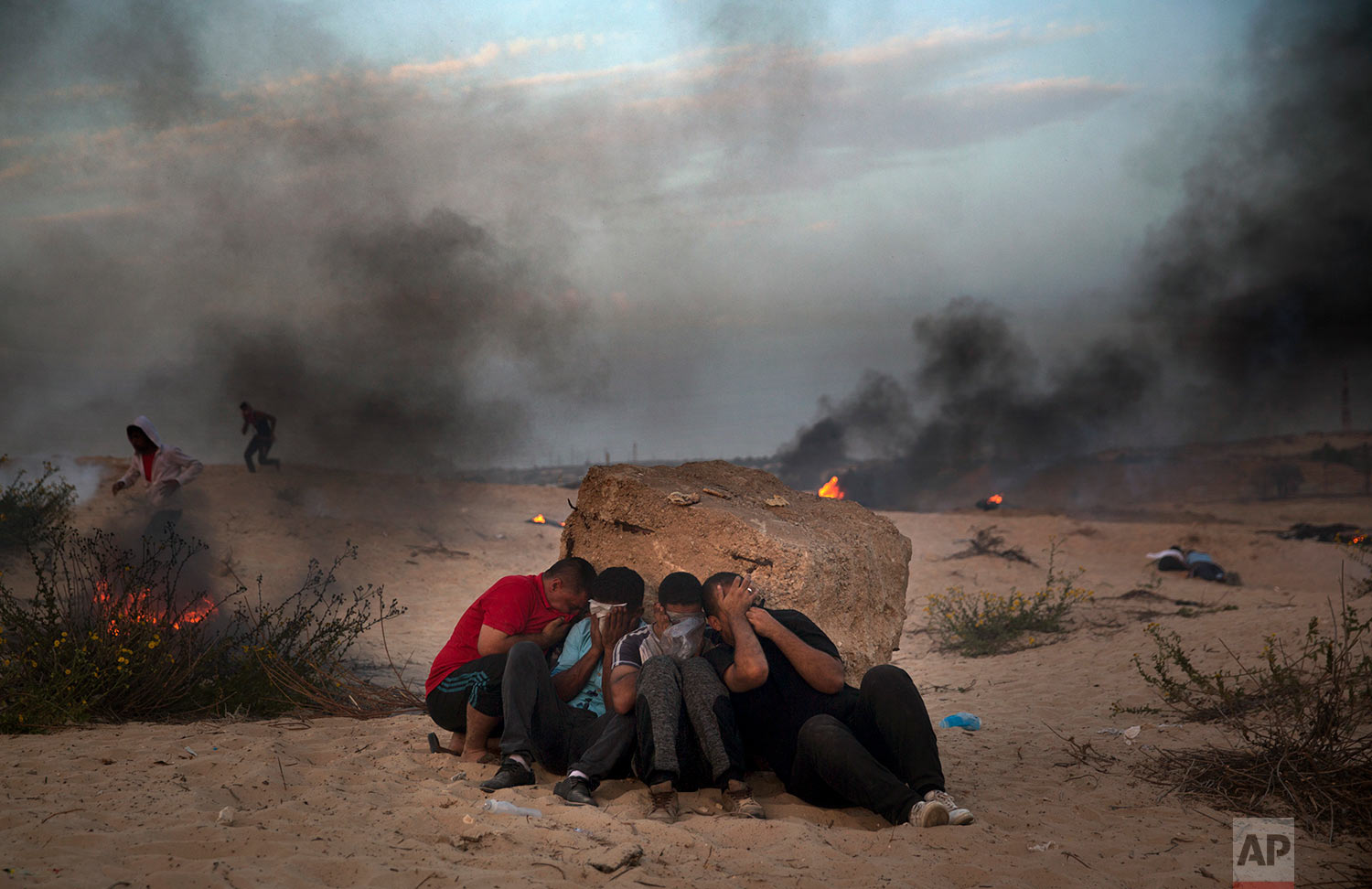Palestinian protesters cover their faces from teargas fires by Israeli troops during a protest on the beach at the border with Israel near Beit Lahiya, northern Gaza Strip, Oct. 22, 2018. (AP Photo/Khalil Hamra)
