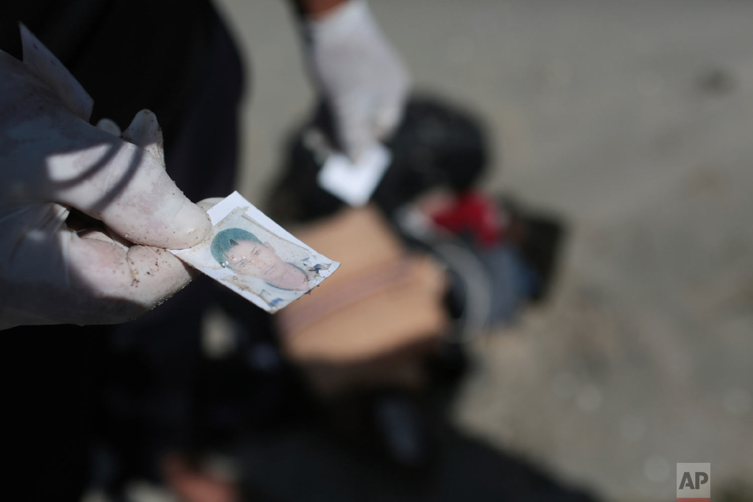 A Libyan Red Crescent worker holds a picture that was found in a bag of belongings that washed up on a beach near the Tunisian Libyan border, not far from Zuwarah, 102 km (63 mi) west of Tripoli, Libya, Saturday, Sept. 12, 2015.  (AP Photo/Mohamed Ben Khalifa)