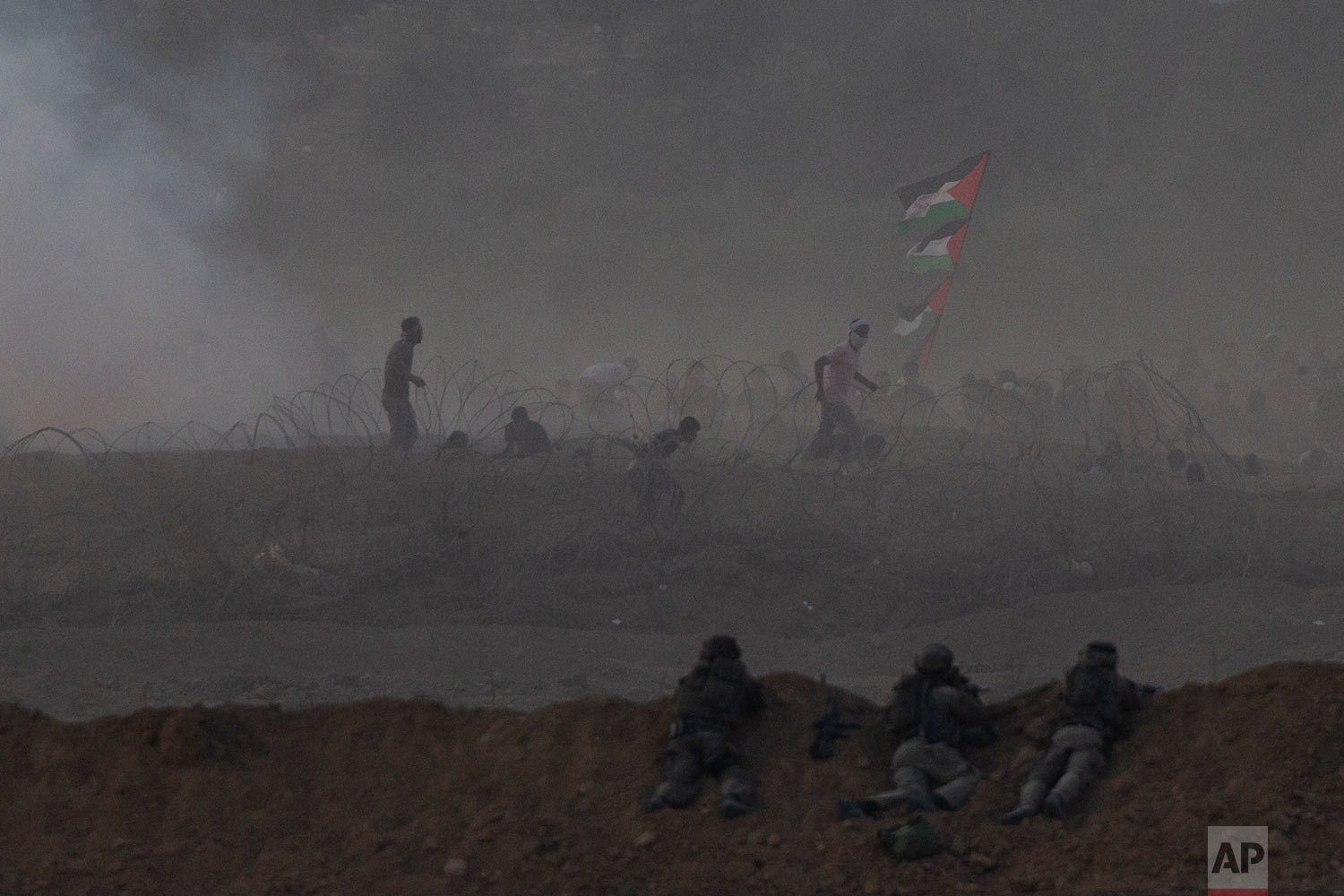 Israeli soldiers are positioned on a sand berm as Palestinian protesters run during a protest along the Israel Gaza border in Israel, Friday, Oct. 19, 2018. (AP Photo/Ariel Schalit)