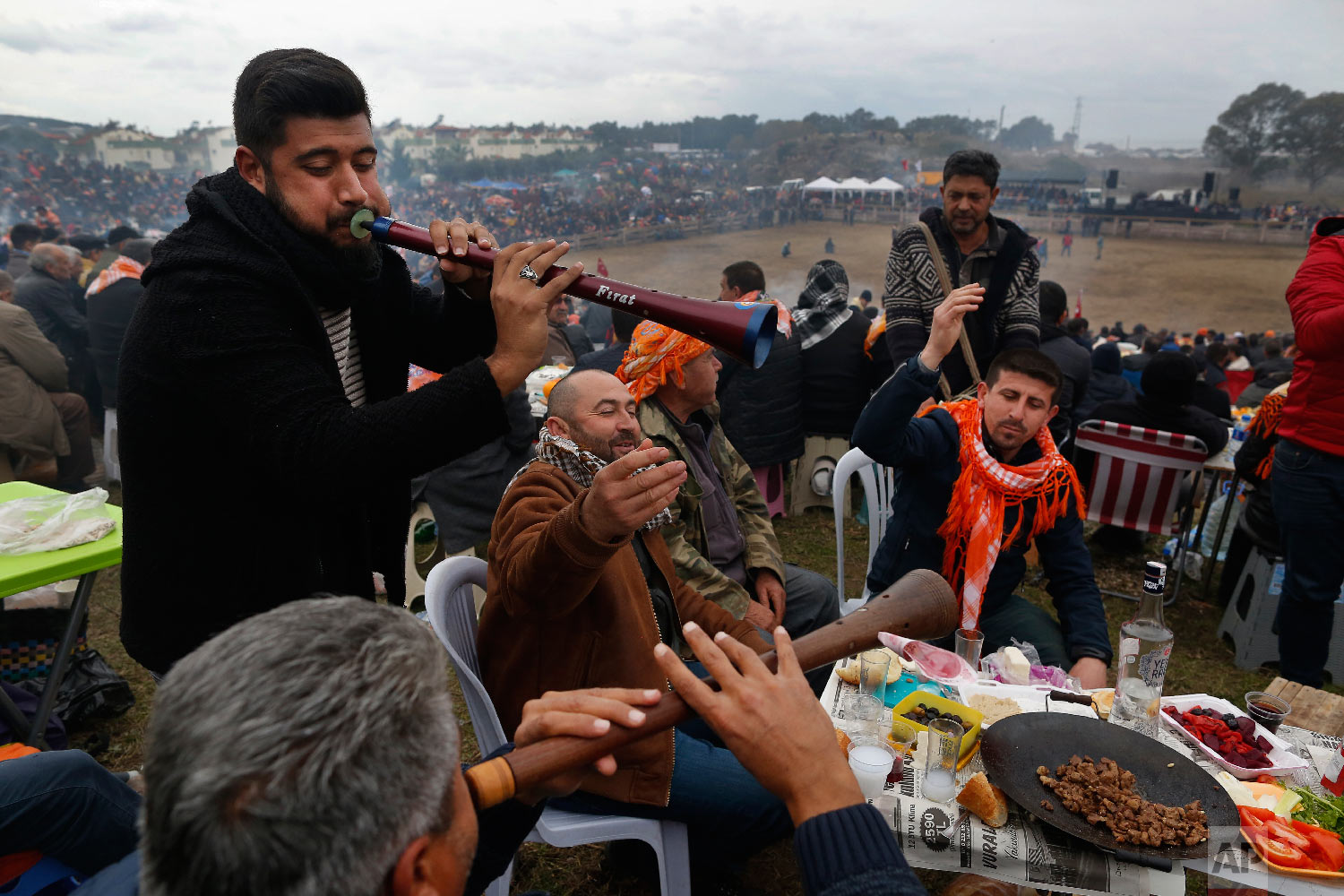Musicians perform traditional folk songs, as spectators enjoy on a hill overlooking an arena where camels wrestle during Turkey's largest camel wrestling festival in the Aegean town of Selcuk, Turkey, Sunday, Jan. 20, 2019.  (AP Photo/Lefteris Pitarakis)
