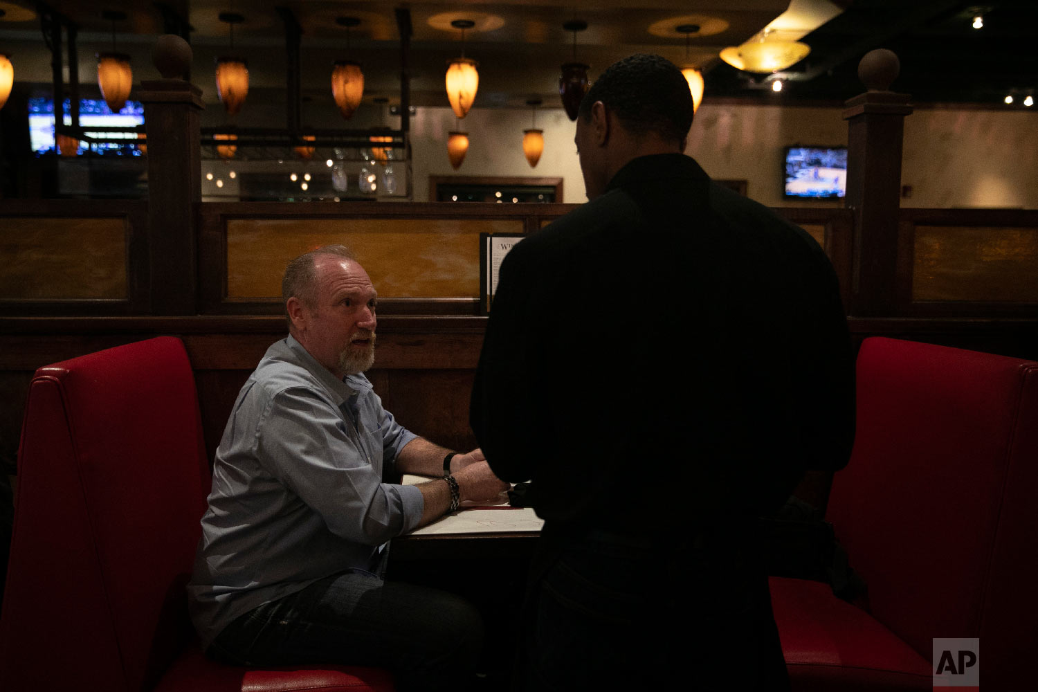 Chris George, a federal employee furloughed from his job as a forestry technician supervisor for the U.S. Department of Agriculture Forest Service, orders his meal at a Romano's Macaroni Grill restaurant Saturday, Jan. 19, 2019, in Redlands, Calif. (AP Photo/Jae C. Hong)
