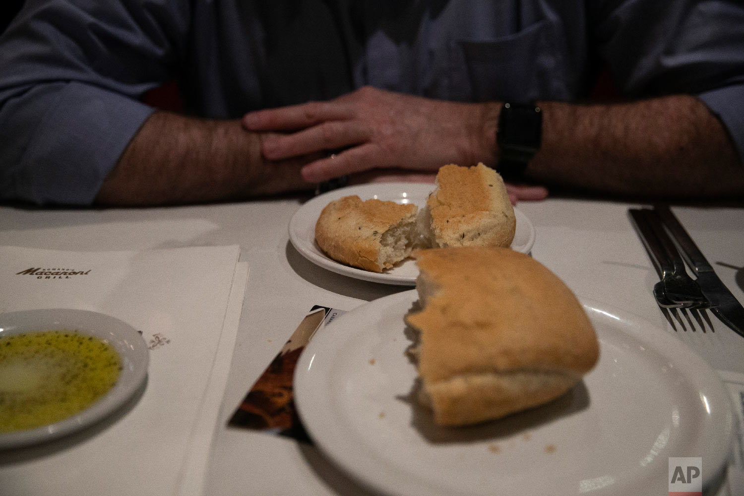 Chris George, a federal employee furloughed from his job as a forestry technician supervisor for the U.S. Department of Agriculture Forest Service, waits for his meal at a Romano's Macaroni Grill restaurant Saturday, Jan. 19, 2019, in Redlands, Calif. (AP Photo/Jae C. Hong)