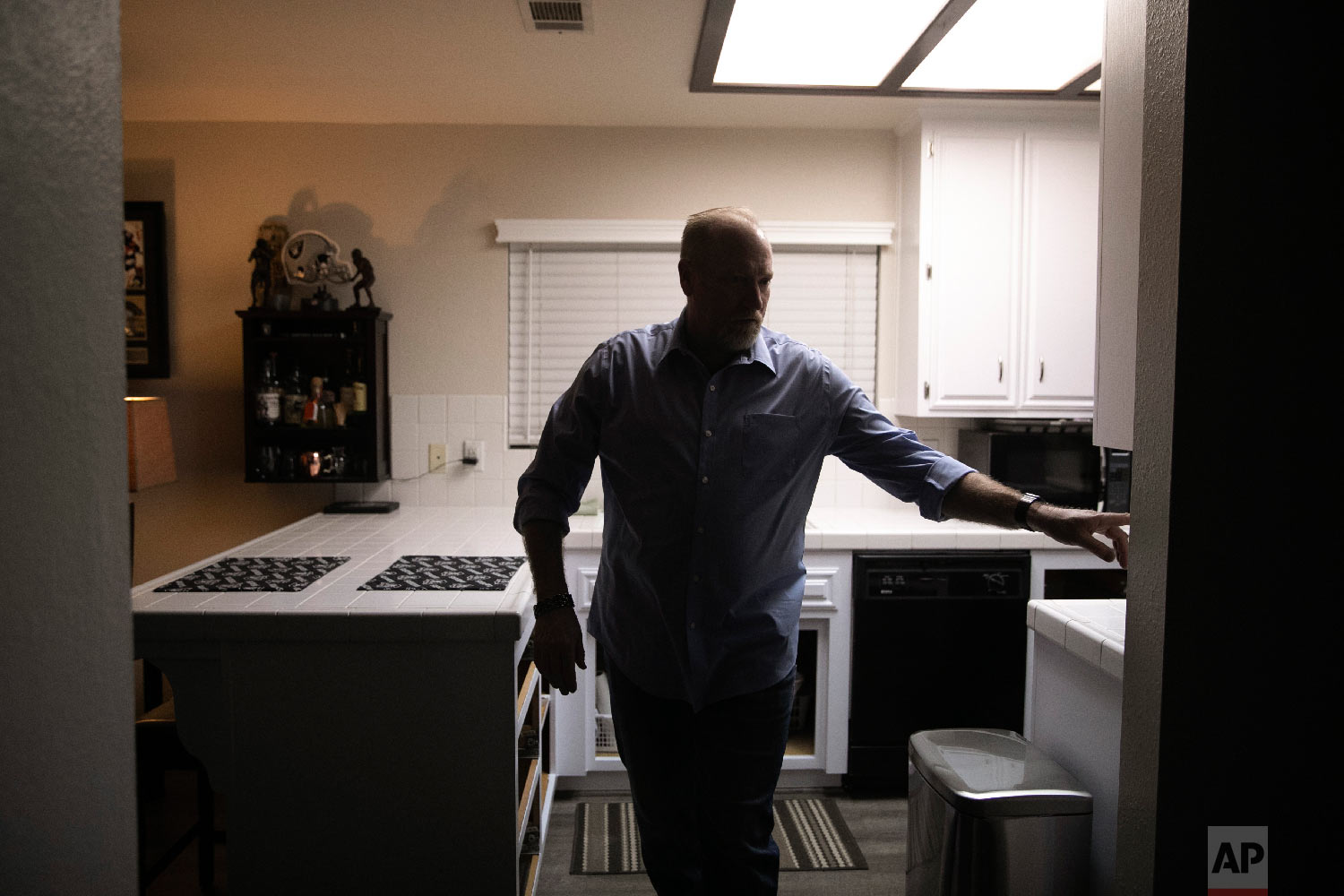 Chris George, a federal employee furloughed from his job as a forestry technician supervisor for the U.S. Department of Agriculture Forest Service, turns the kitchen lights off as he leaves home for a free meal offered to federal workers affected by the government shutdown Saturday, Jan. 19, 2019, in Hemet, Calif. (AP Photo/Jae C. Hong)