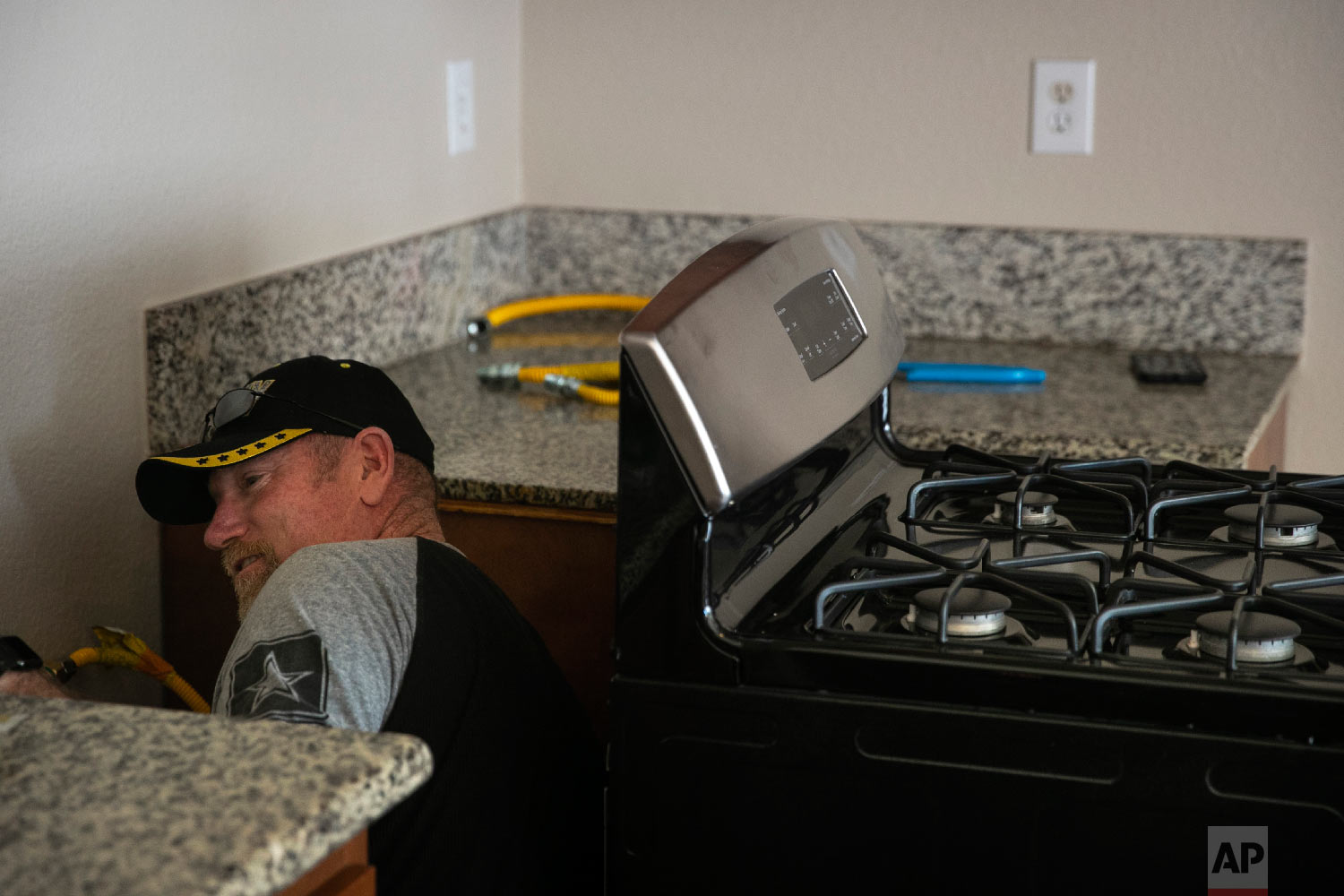 Chris George, a federal employee furloughed from his job as a forestry technician supervisor for the U.S. Department of Agriculture Forest Service, installs a gas stove Saturday, Jan. 19, 2019, in Fontana, Calif. (AP Photo/Jae C. Hong)