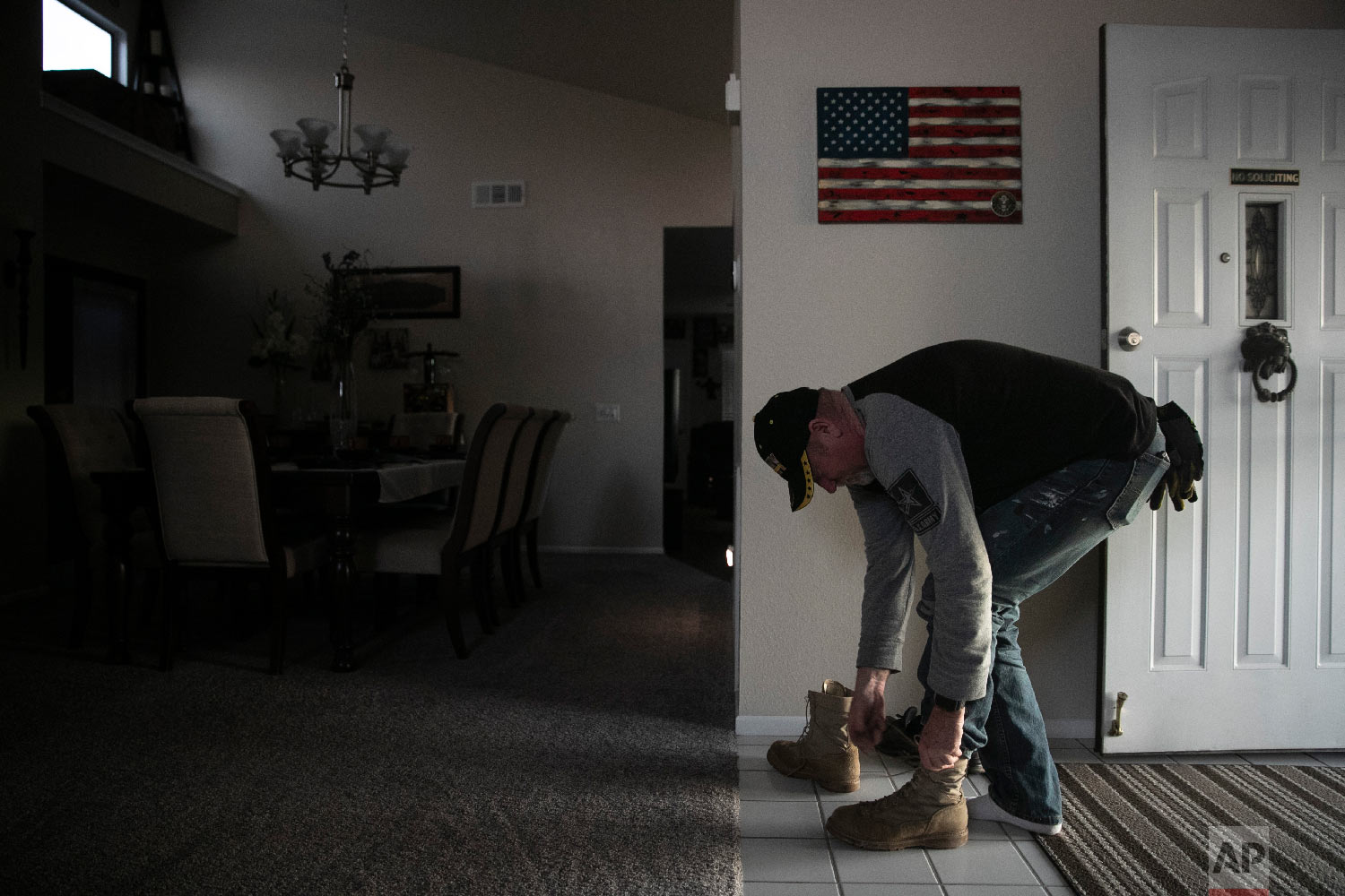 Chris George, a federal employee furloughed from his job as a forestry technician supervisor for the U.S. Department of Agriculture Forest Service, takes off his boots at his home adorned with an American flag after spending the day working as a handyman Saturday, Jan. 19, 2019, in Hemet, Calif. (AP Photo/Jae C. Hong)