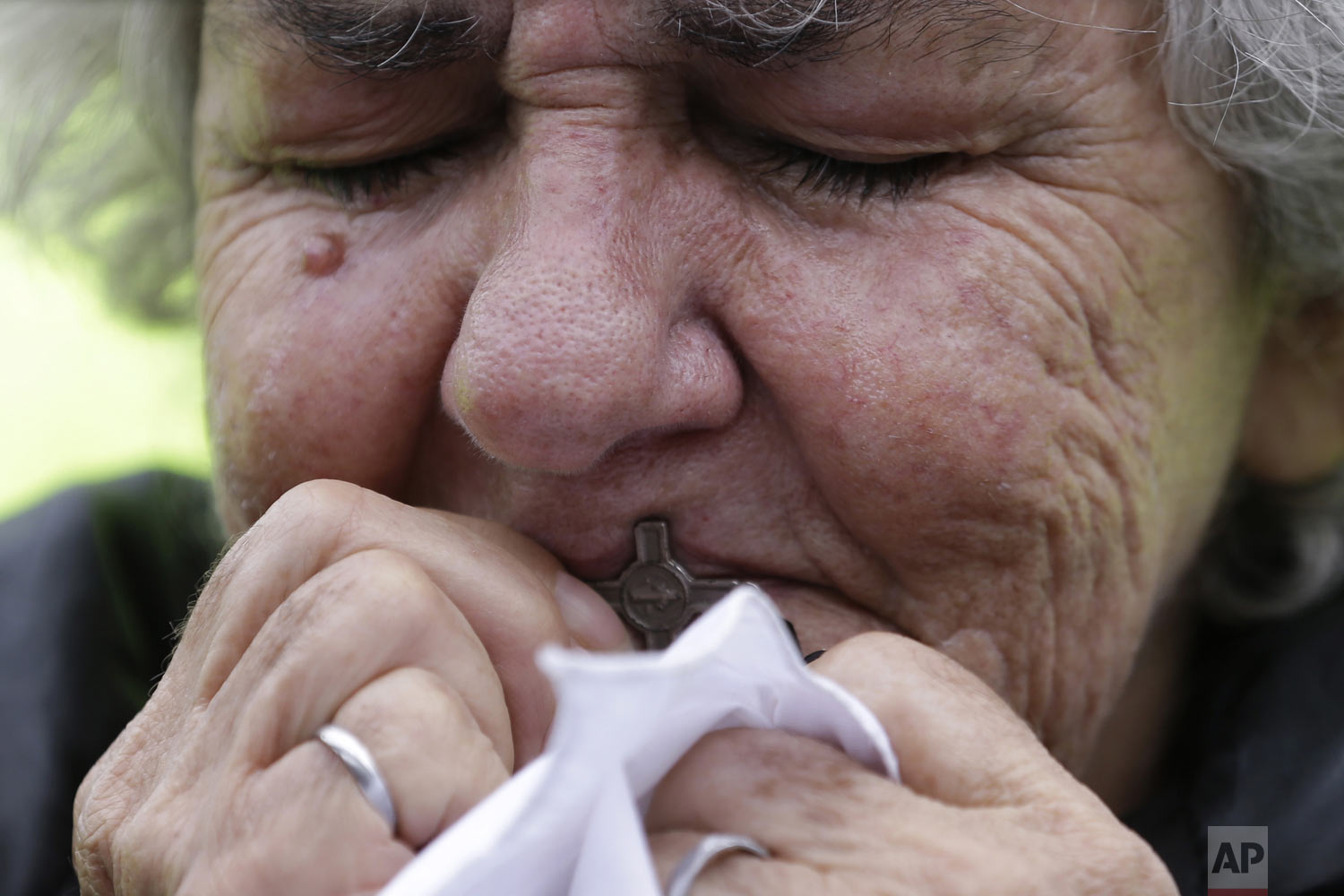 A woman kisses a cross during a rally to repudiate terrorism in Bolivar Square in Bogota, Colombia, Sunday, Jan. 20, 2019. The National Liberation Army claimed responsibility Monday for the deadly car bombing, stating the attack against a military installation was a legitimate response to the armed forces' bombing of a guerrilla camp during a recent unilateral ceasefire. (AP Photo/Fernando Vergara)