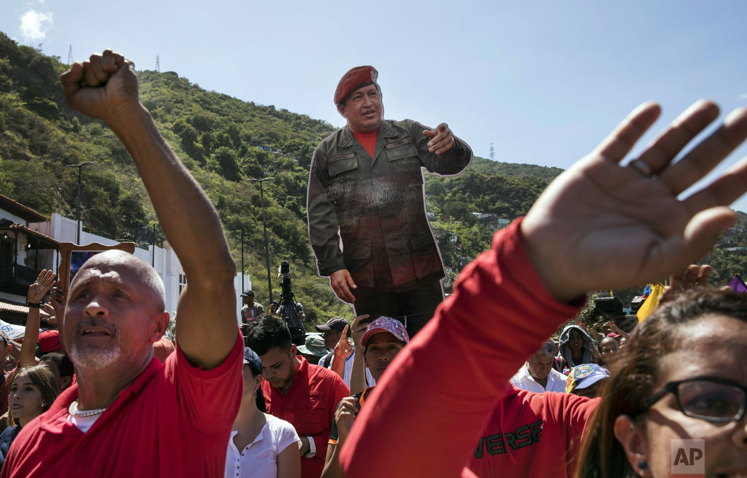 Government supporters hold a life-size image of Venezuela's late President Hugo Chavez during a rally in La Guaira, Venezuela, Friday, Jan. 25, 2019. Venezuelan President Nicolas Maduro, Chavez's protege, says he's willing to engage in talks with the opposition in order to avoid violence in a conflict over who is the legitimate leader of the country. (AP Photo/Rodrigo Abd)