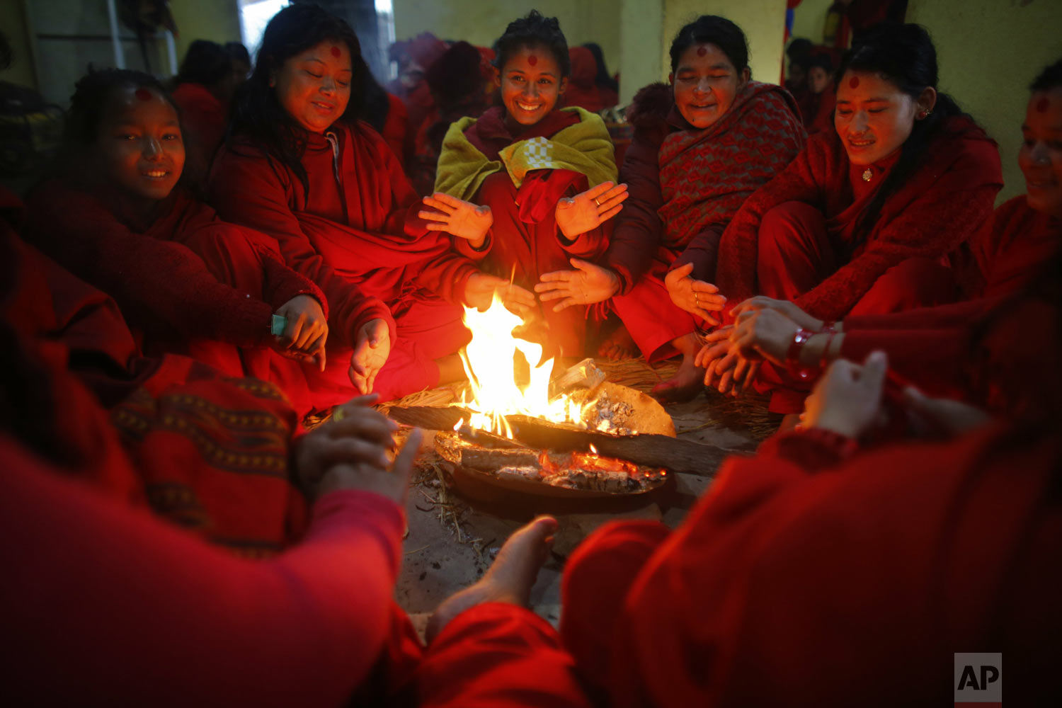 Devotees warm themselves up around a fire after taking a holy dip in the Sali River during Madhav Narayan festival in Sankhu, northeast of Kathmandu, Nepal, on Monday, Jan. 21, 2019. During the festival, worshippers recite holy scriptures dedicated to Hindu goddess Swasthani and Lord Shiva. Unmarried women pray for a good husband while those married pray for the longevity of their husbands by observing a month-long fast. (AP Photo/Niranjan Shrestha)