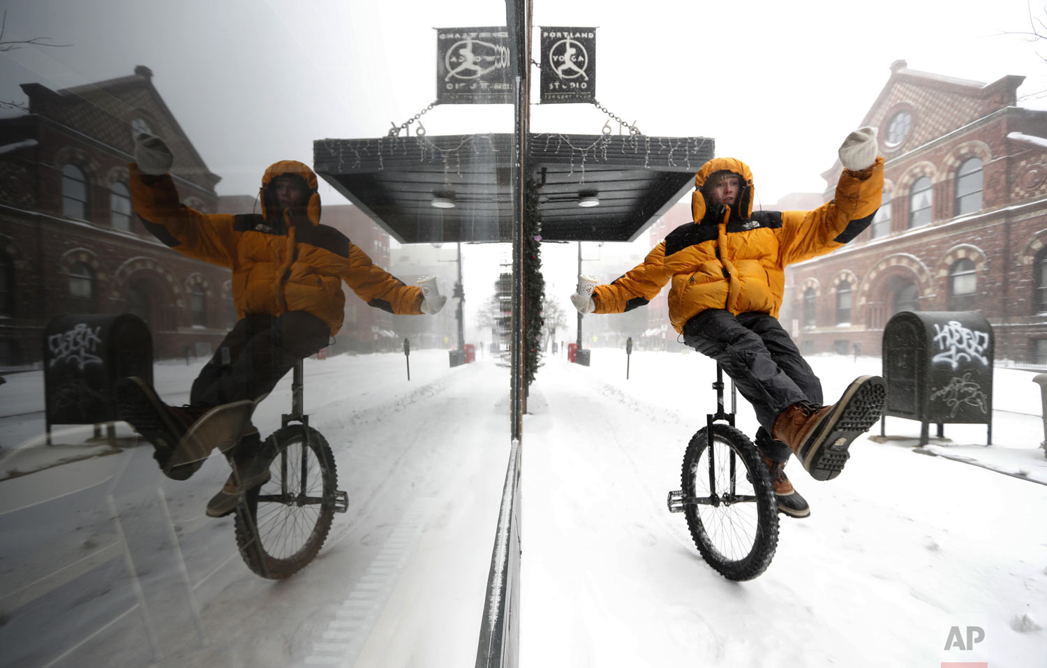 Caleb Seely rides a unicycle on a snow-covered sidewalk as he heads home after helping shovel out his brother's driveway during a winter storm, Sunday, Jan. 20, 2019, in Portland, Maine. The extra knobby tire on Seely's ride provided traction on a day when snow, sleet and freezing rain kept most motorists indoors. (AP Photo/Robert F. Bukaty)