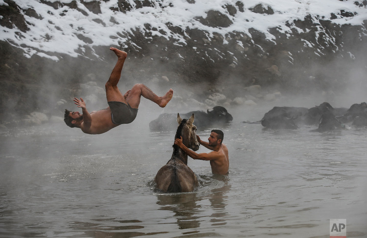 Muhammed Toren, 18, left, and Berkan Toren, 20, enjoy a hot spring along with their water buffaloes near the village of Budakli, in the mountainous Bitlis province of eastern Turkey, Thursday, Jan. 24, 2019. (AP Photo/Emrah Gurel)