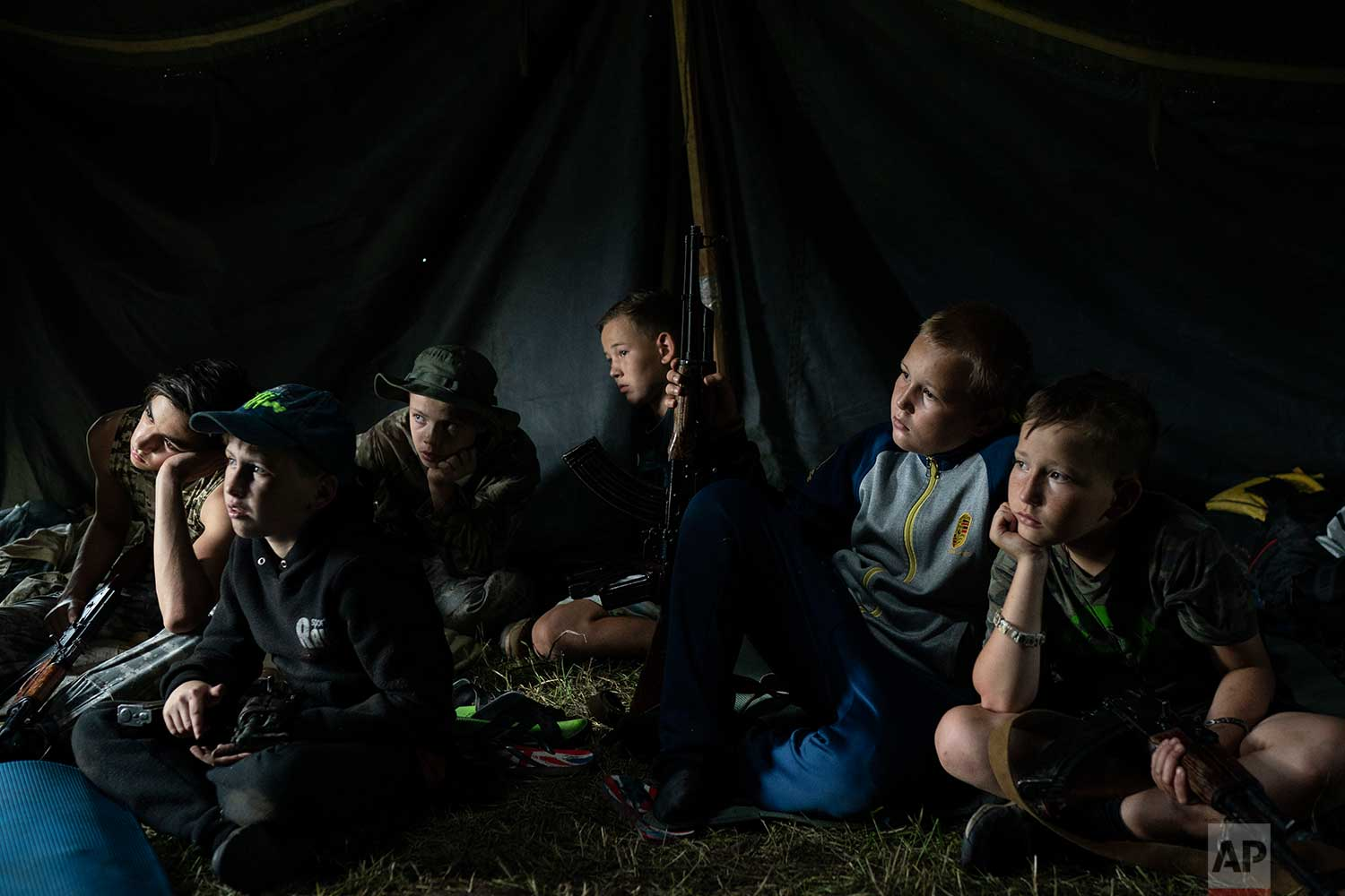 """In this July 28, 2018 photo, young participants of the """"Temper of will"""" summer camp, organized by the nationalist Svoboda party, sit inside a tent with their AK-47 riffles as they receive instructions during a tactical exercise in a village near Ternopil, Ukraine. (AP Photo/Felipe Dana)"""