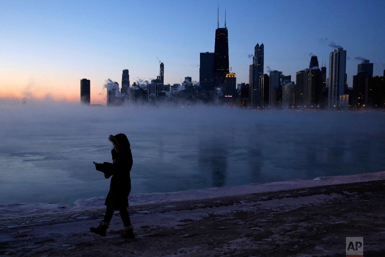 A person walks along the lakeshore, Wednesday, Jan. 30, 2019, in Chicago. (AP Photo/Kiichiro Sato)