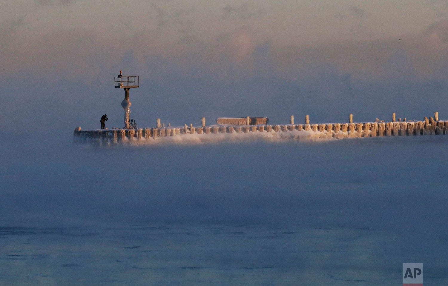 A harbor light is covered by snow and ice on the Lake Michigan at 39th Street Harbor, Wednesday, Jan. 30, 2019, in Chicago. (AP Photo/Nam Y. Huh)