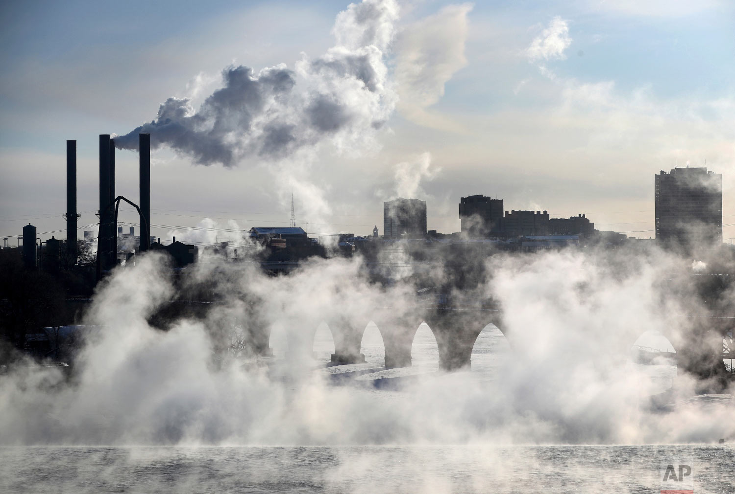 Water vapor rises above St. Anthony Falls on the Mississippi River as the Stone Arch Bridge is obscured, seen from the Third Ave. Bridge Tuesday, Jan. 29, 2019, In Minneapolis. (David Joles/Star Tribune via AP)