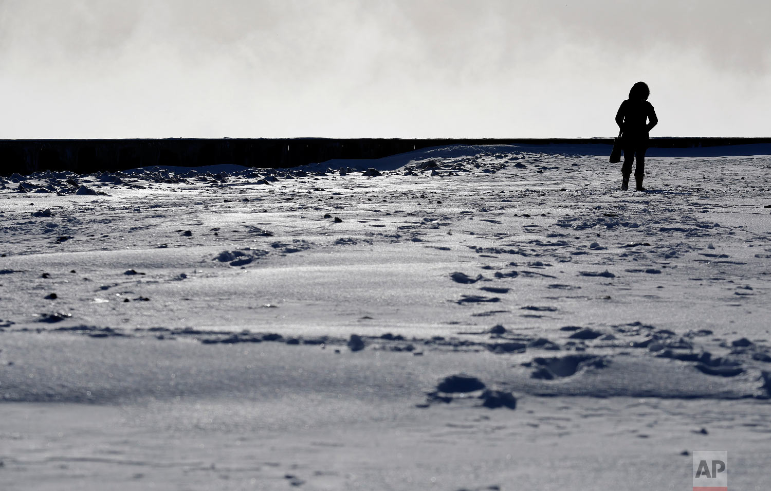 A woman walks along the shore of Lake Michigan at the Lighthouse Park in Evanston, Ill., Wednesday, Jan. 30, 2019.  (AP Photo/Nam Y. Huh)