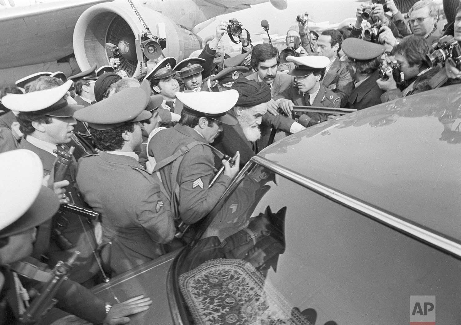 In this Feb. 1, 1979 photo, exiled Ayatollah Ruhollah Khomeini has a heavy escort as he enters car to leave the airport in Tehran, Iran. (AP Photo)