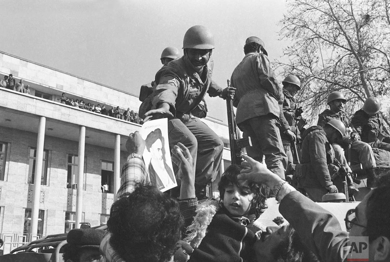 In this Jan. 15, 1979 photo, a smiling Iranian soldier is hailed by demonstrators who decorated them with flowers and pictures of Ayatollah Ruhollah Khomeini, in Tehran, Iran.  (AP Photo)