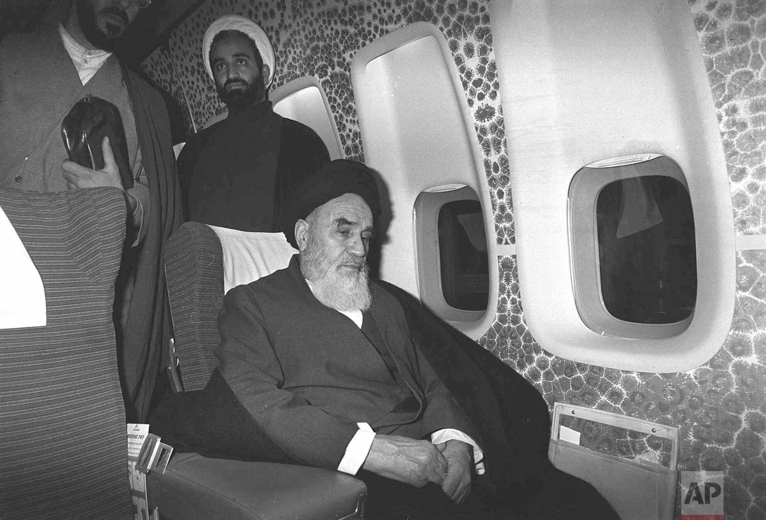 In this Feb. 1, 1979 photograph, Ayatollah Ruhollah Khomeini sits inside the chartered airplane which will fly him back to Iran, a few minutes before the plane took off from Paris, France. (AP Photo/Campion)