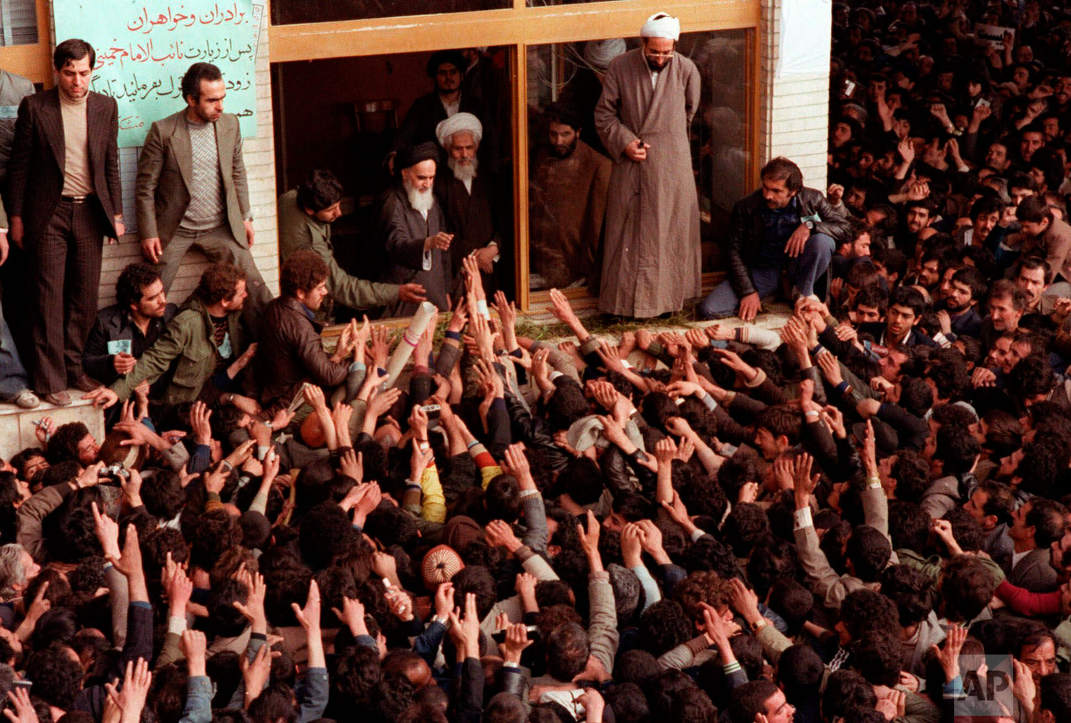 In this Feb. 2, 1979 photo, Ayatollah Ruhollah Khomeini, center, is greeted by supporters in Tehran, Iran. (AP Photo)