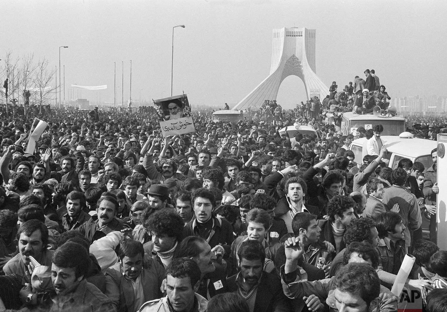 In this Feb. 1, 1979 photo, the motorcade of Ayatollah Ruhollah Khomeini is lost among the throngs of supporters at the Shayad, a landmark memorial to the shah, near the airport in Tehran, Iran. (AP Photo/FY)