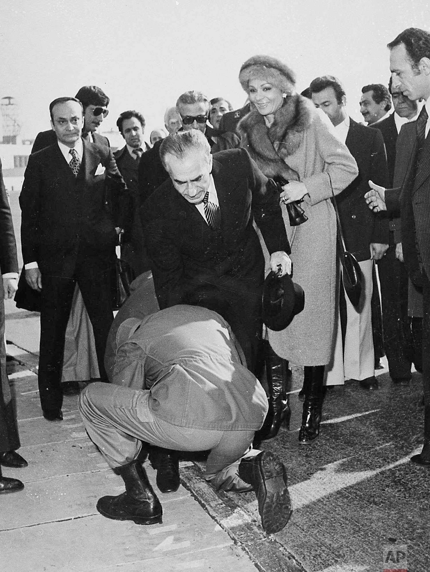 In this Jan. 16, 1979 photo, a soldier bends to kiss the feet of Iran's Shah Mohammad Reza Pahlavi on the tarmac of Mehrabad Airport in Tehran, Iran. Behind the shah is his wife, Empress Farah. (AP Photo)
