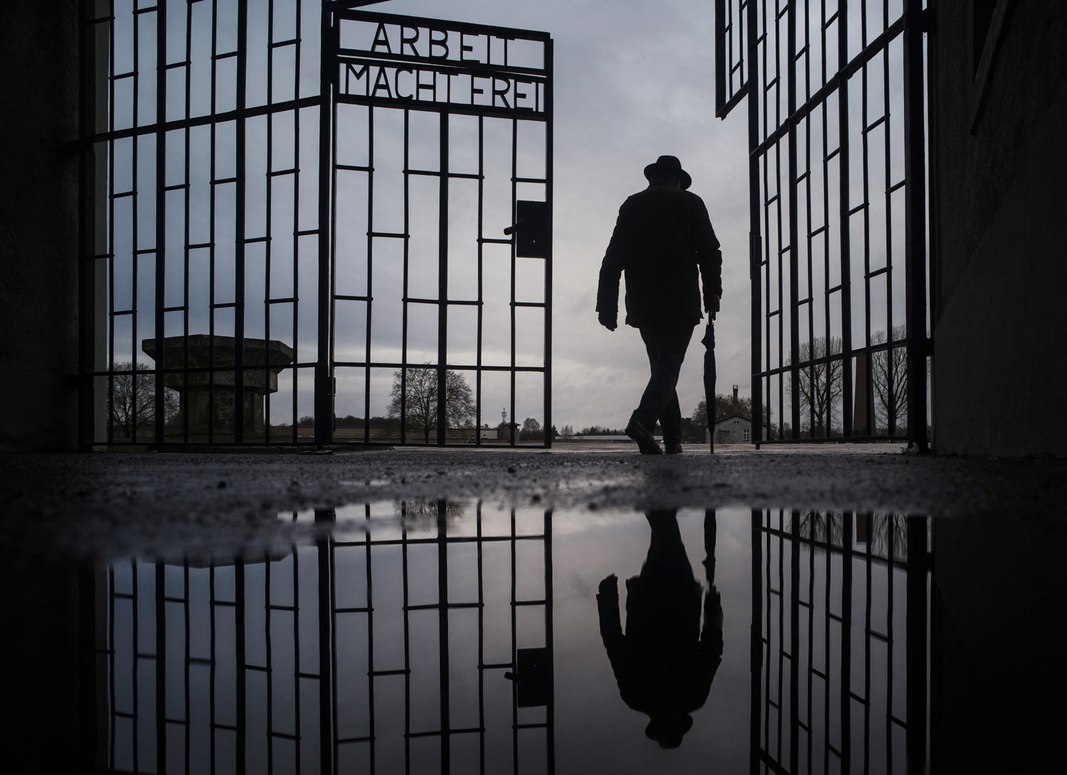 A man walks through the gate of the Sachsenhausen Nazi death camp with the phrase 'Arbeit macht frei' (work sets you free) during International Holocaust Remembrance Day in Oranienburg, about 30 kilometers (18 miles), north of Berlin, Germany, on Sunday, Jan. 27, 2019. The anniversary marks the liberation of the Auschwitz Nazi death camp on Jan. 27, 1945. (AP Photo/Markus Schreiber)