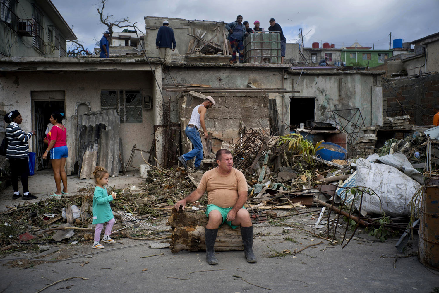 A man rests on the trunk of a tree that was toppled by a tornado, after removing rubble from his home in Regla, Cuba, on Monday, Jan. 28, 2019. A tornado and pounding rains smashed into the eastern part of Cuba's capital overnight, toppling trees, bending power poles and flinging shards of metal roofing through the air as the storm cut a path of destruction across eastern Havana. (AP Photo/Ramon Espinosa)