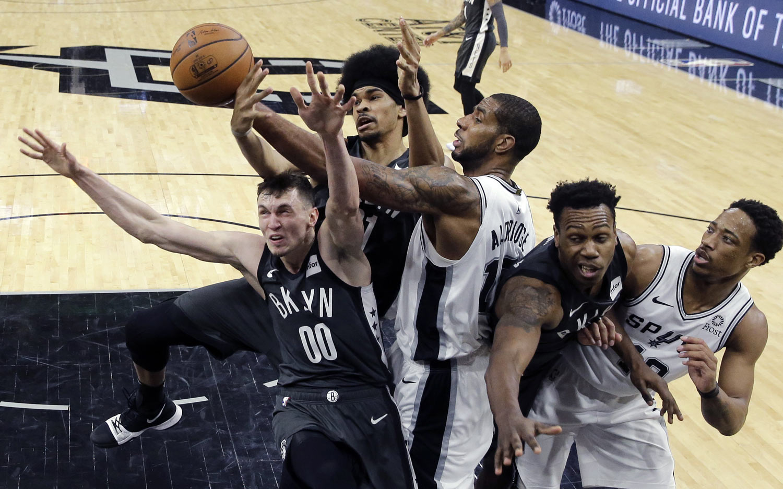 San Antonio Spurs center LaMarcus Aldridge (12) battles Brooklyn Nets forward Rodions Kurucs (00) and center Jarrett Allen, second from left, for a rebound during the second half of an NBA basketball game, in San Antonio, Thursday, Jan. 31, 2019. San Antonio won 117-114. (AP Photo/Eric Gay)