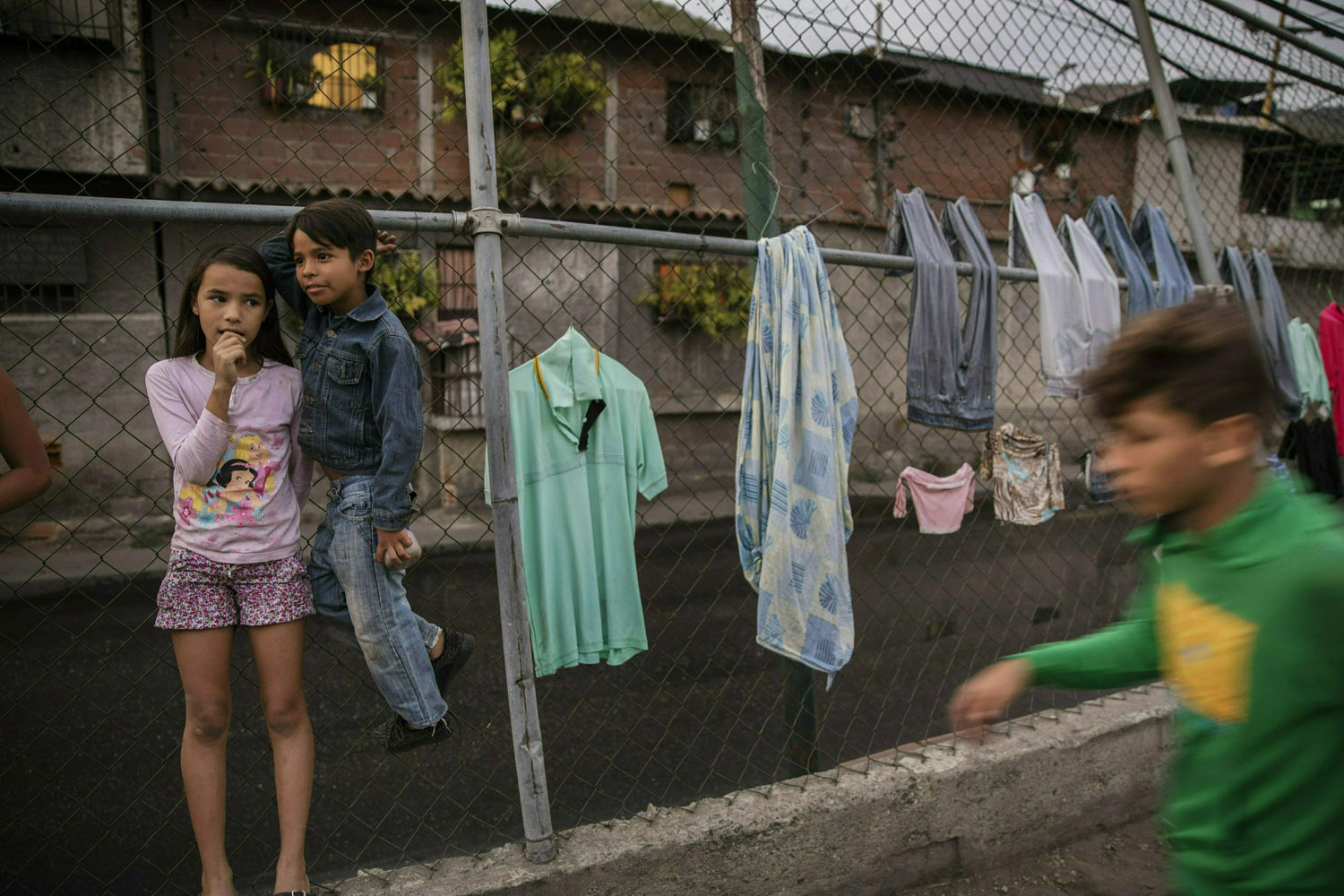 Valentina Gonzalez, 10, left, and her friend Engleston Gonzalez, 8, stand next to clothes drying on a fence in Caracas, Venezuela, Tuesday, Jan. 29, 2019. Venezuela's President Nicolas Maduro went on state television Tuesday to announce that he was beefing up the nation's defense by expanding Venezuela's civilian armed militia to 2 million members. The reserve force was created by the late Hugo Chavez to train civilians to assist the armed forces and defend the socialist revolution from attacks. (AP Photo/Rodrigo Abd)