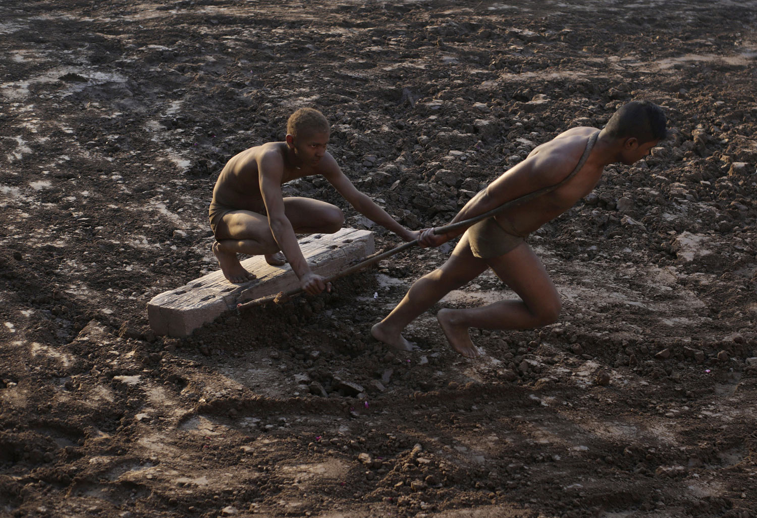 Wrestlers prepare the ground as part of their training for the national sport of Kushti, in Lahore, Pakistan, Monday, Jan. 28, 2019. Kushti, also known as Pehlwani, is a several thousand year-old sport and is practiced in the Indian subcontinent. The wrestlers train and compete on dirt floors, cleared of stones and dyed red. (AP Photo/K.M. Chaudary)