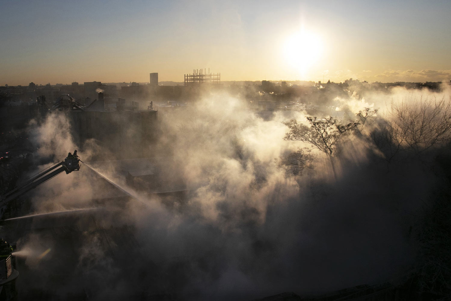 Firefighters spray water onto a burning a commercial building in the Bedford Stuyvesant neighborhood of Brooklyn, New York, on  Thursday, Jan. 31, 2019 during extremely cold temperatures in the area. (AP Photo/Mark Lennihan)