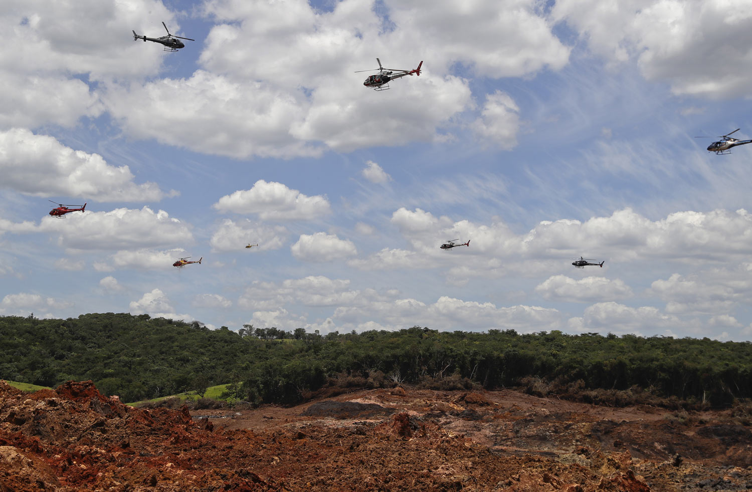 Helicopters hover over an iron ore mining complex to release thousands of flower petals paying homage to the 110 victims killed and 238 who are still missing after a mining dam collapsed there a week earlier, in Brumadinho, Brazil, Friday, Feb. 1, 2019. (AP Photo/Andre Penner)