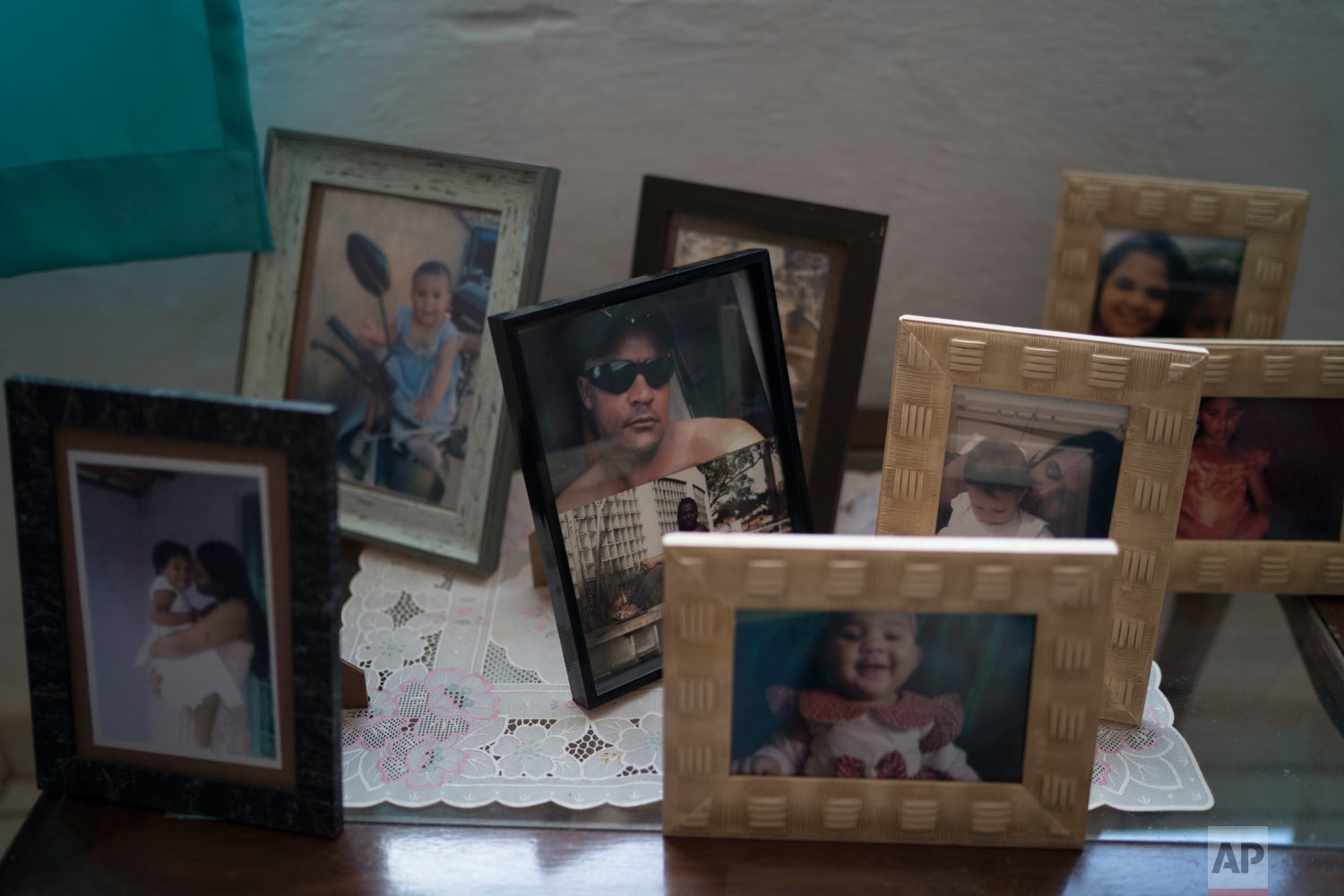 A photo of Peterson Nunes Ribeiro stands amid other family photos in his mother's living room in Brumadinho, Brazil, Jan. 30, 2019. (AP Photo/Leo Correa)