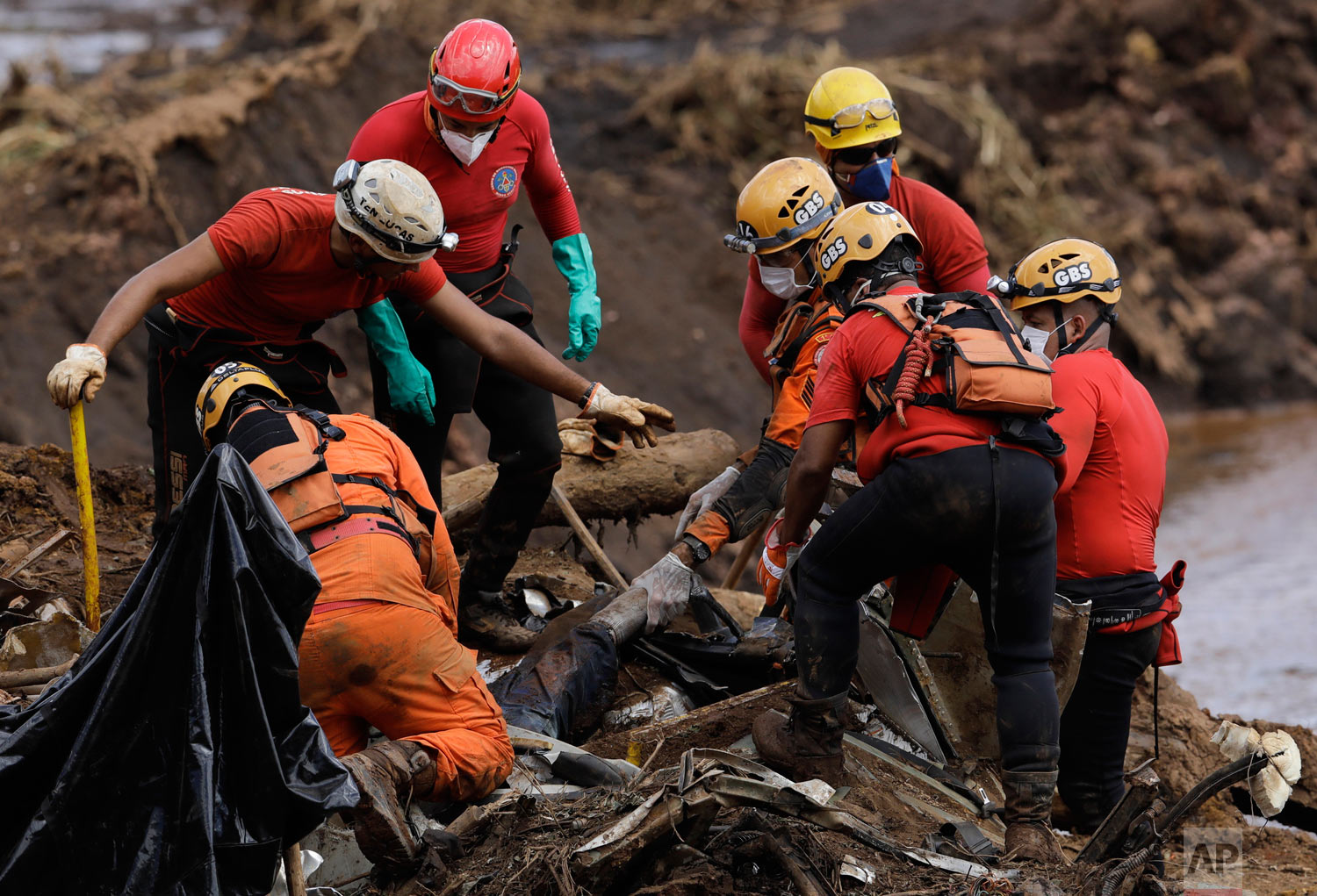 Firefighters pull a body from the mud days after the Vale mining company's dam collapsed in Brumadinho, Brazil, Jan. 28, 2019. (AP Photo/Leo Correa)